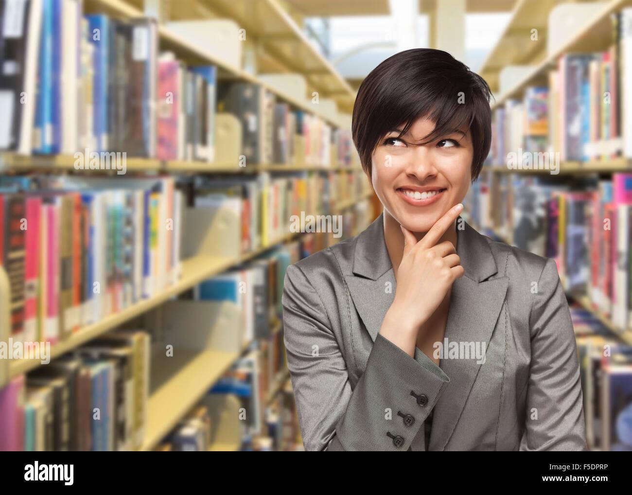 Curieux Mixed Race Girl à la recherche sur le côté de la bibliothèque. Photo Stock