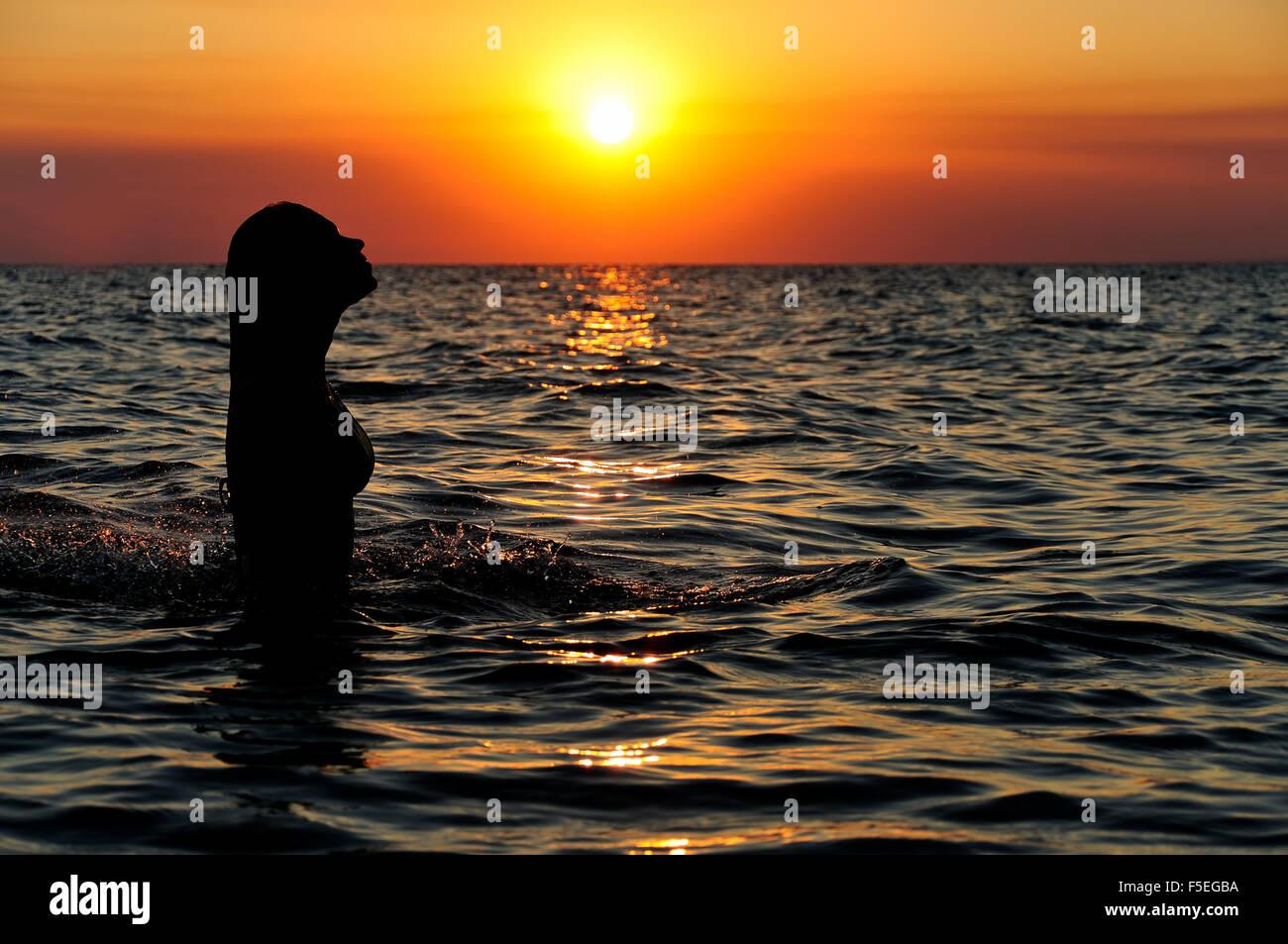 Silhouette d'une femme dans l'océan au coucher du soleil Photo Stock