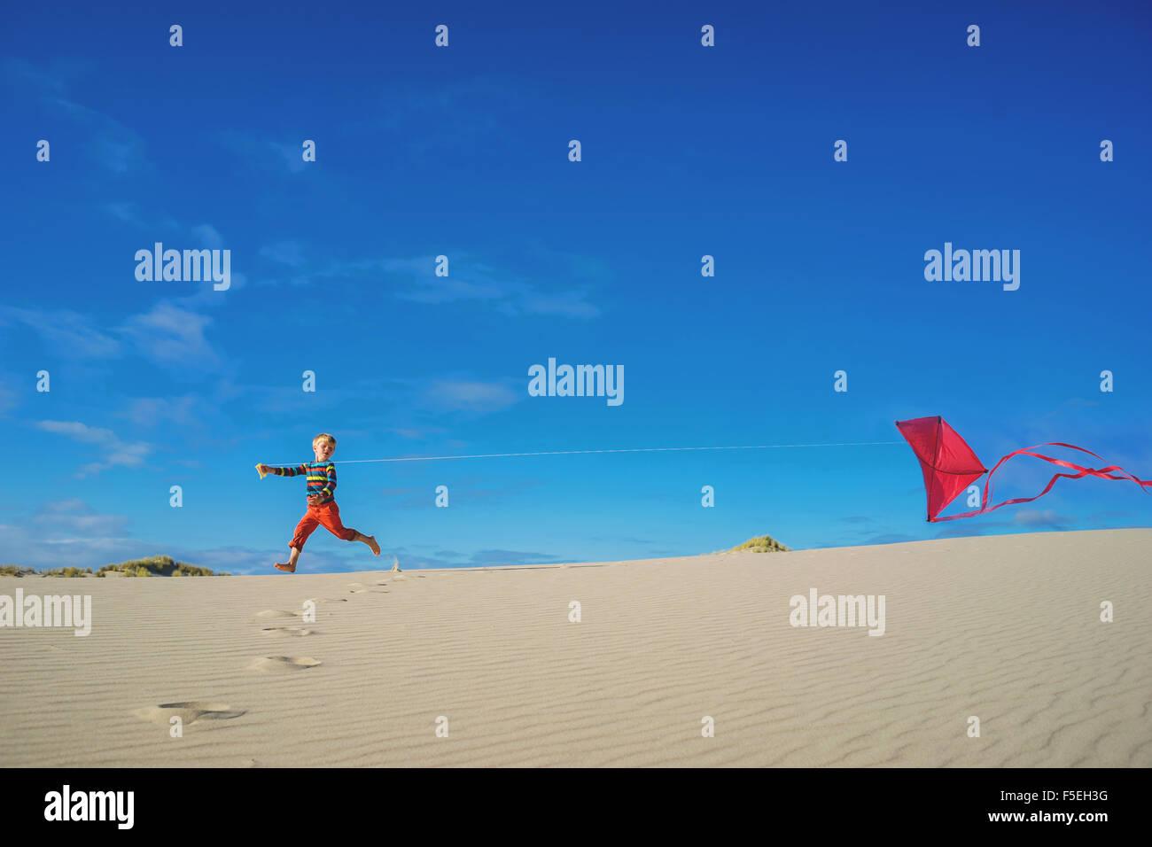 Enfant volant red kite on sandy beach Photo Stock