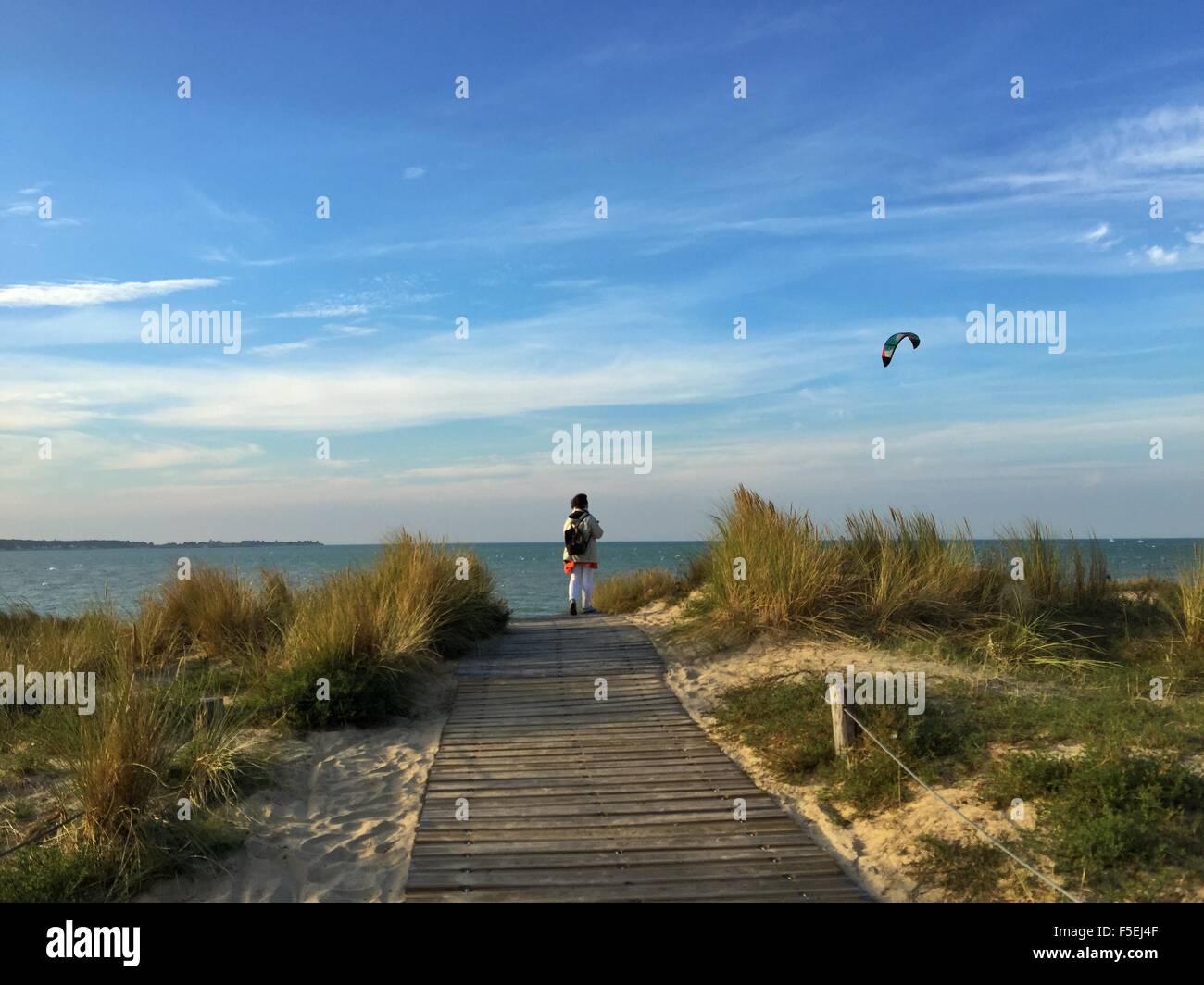 Vue arrière d'une femme debout sur la plage en regardant kiteboarder, La Rochelle, France Photo Stock
