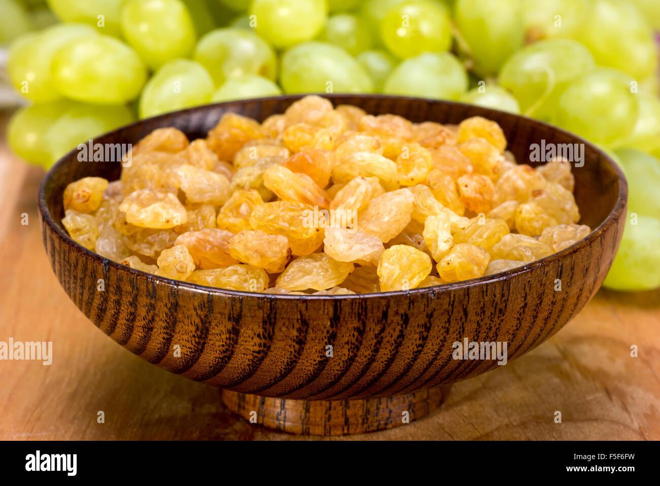 Raisins sans pépins blancs et les raisins secs sultanines dans un bol en bois Banque D'Images