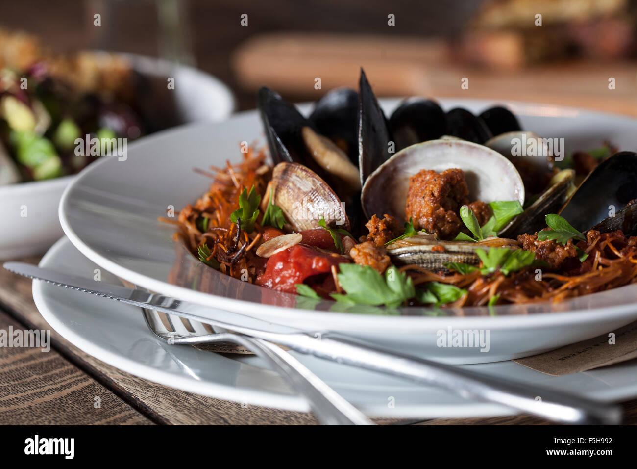 Close-up de moules, palourdes, des pâtes sur une plaque blanche avec fourchette et couteau Banque D'Images