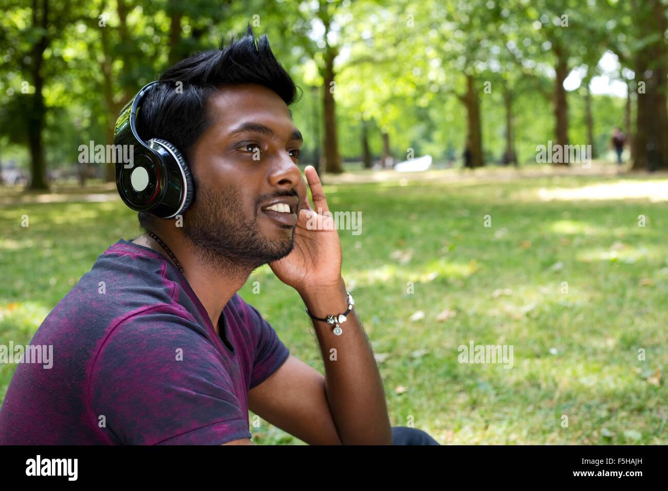 Jeune homme à l'écoute de musique dans le parc Photo Stock