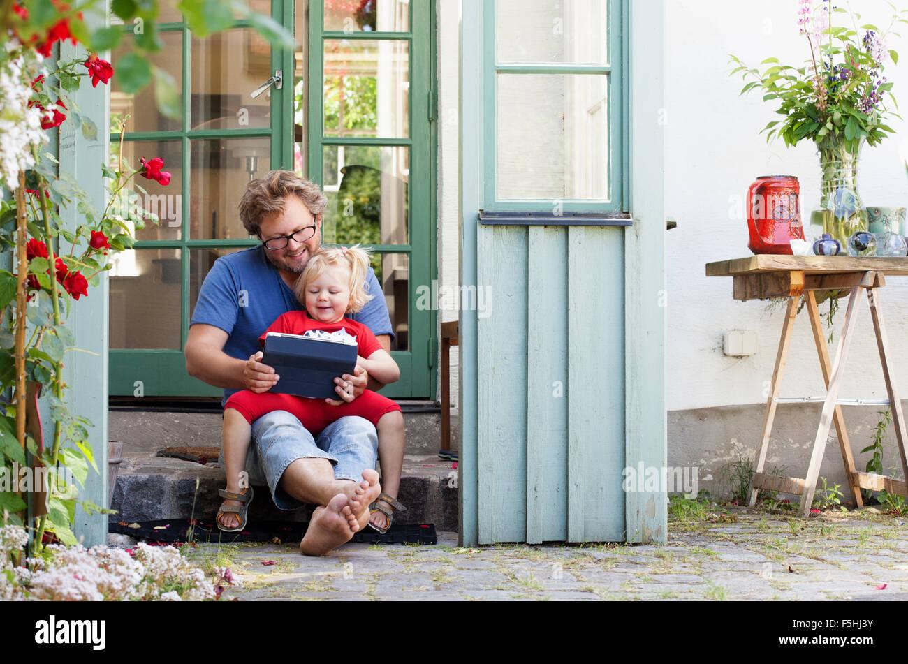 La Suède, Skane, Mossby, fille avec le père assis sur l'étape de pierre et holding tablet pc Photo Stock