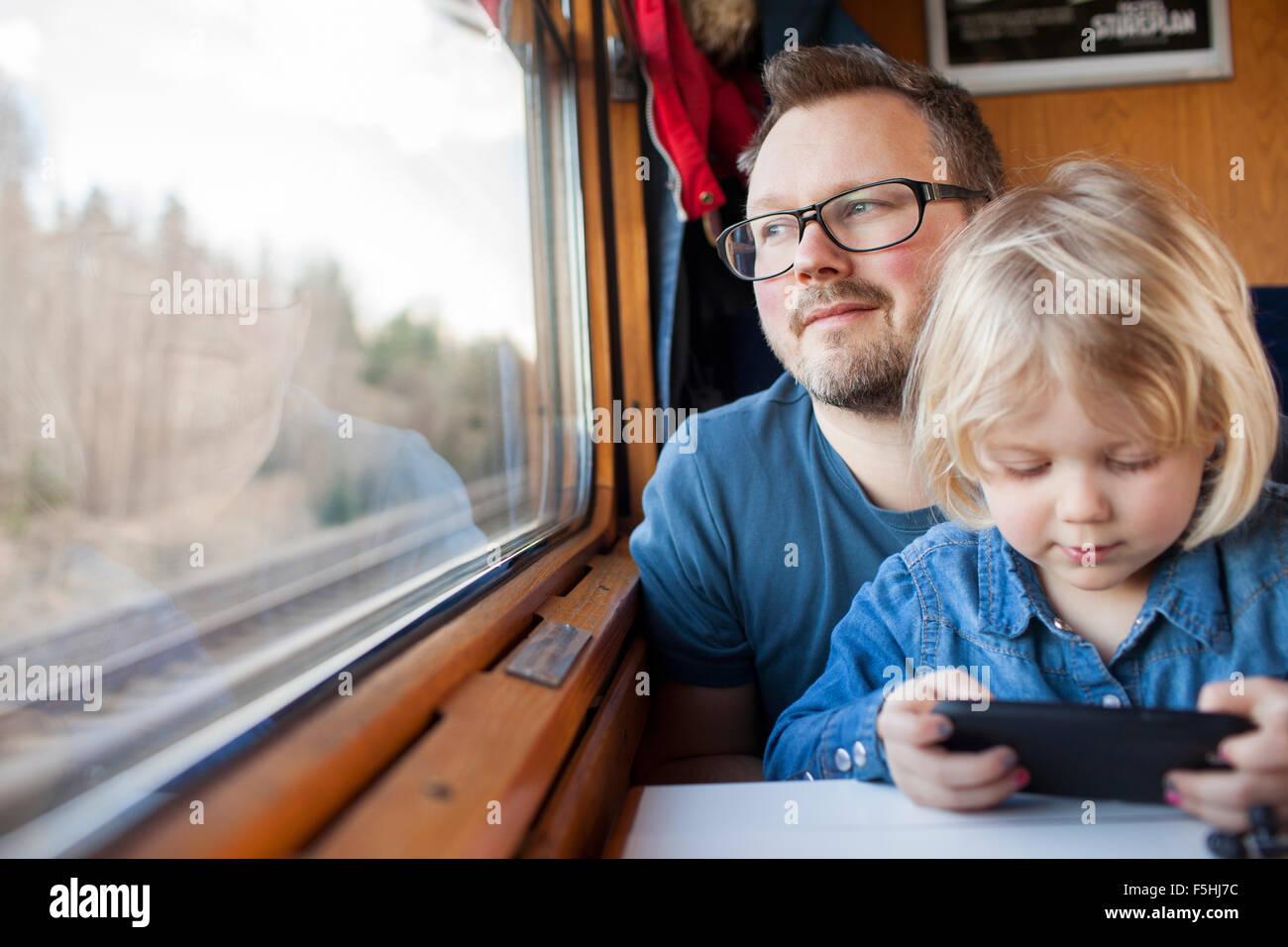La Suède, père et fille (2-3) voyager en train Photo Stock