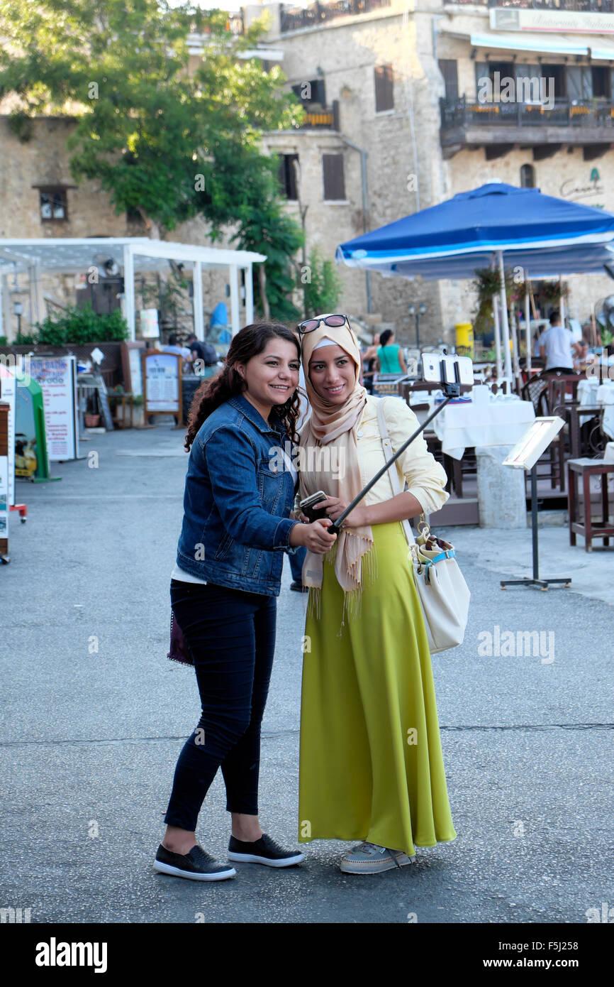 Jeunes femmes musulmanes les amis de prendre une photographie selfies, le long du port de Girne Kyrenia Chypre du Photo Stock