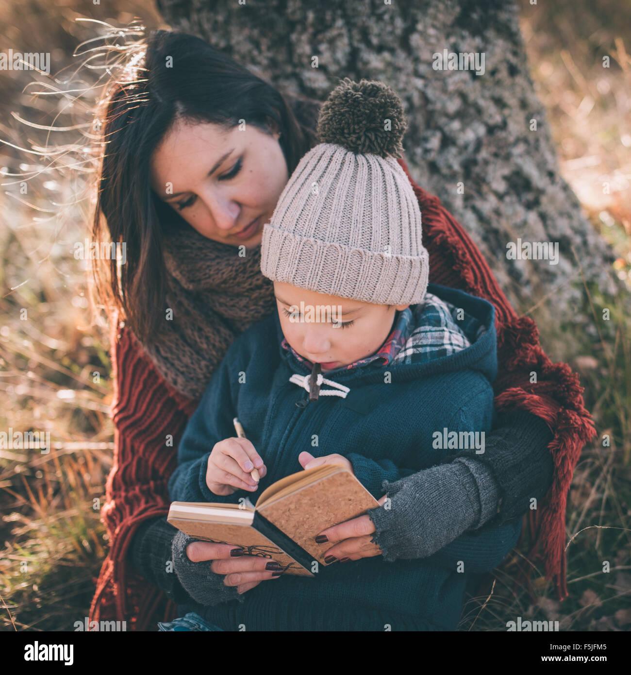 Mère d'aider son fils écrit premières lettres Photo Stock