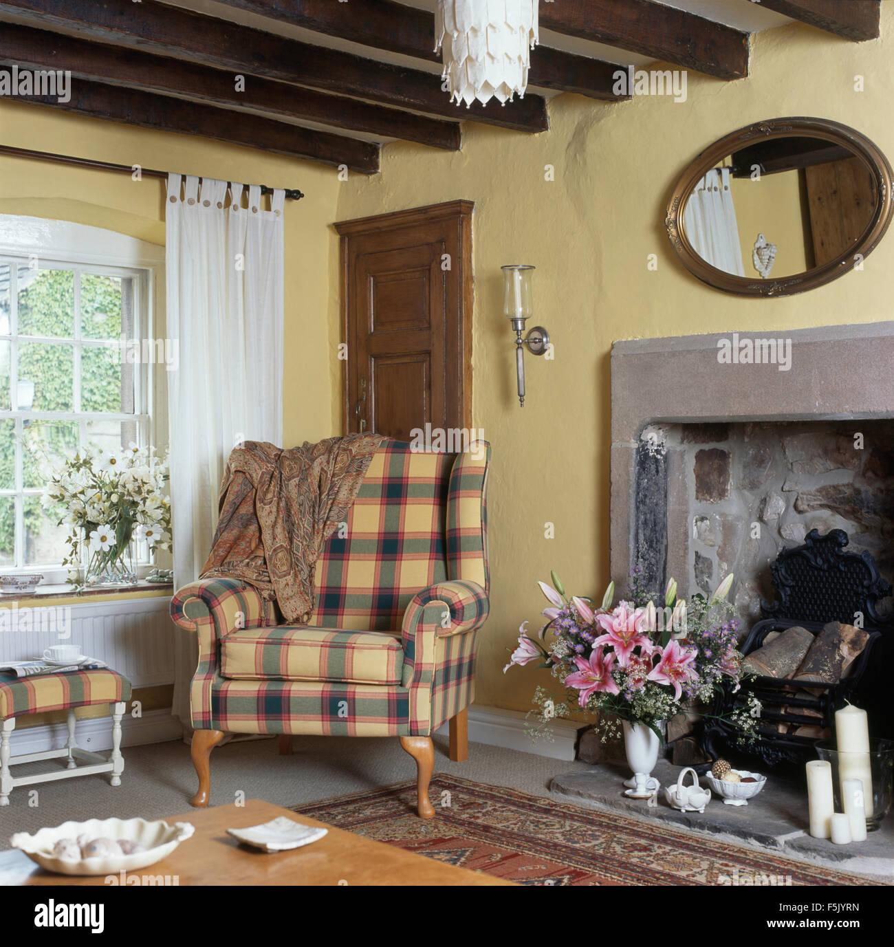 fauteuil à oreilles à carreaux fenêtre avec des rideaux blancs en