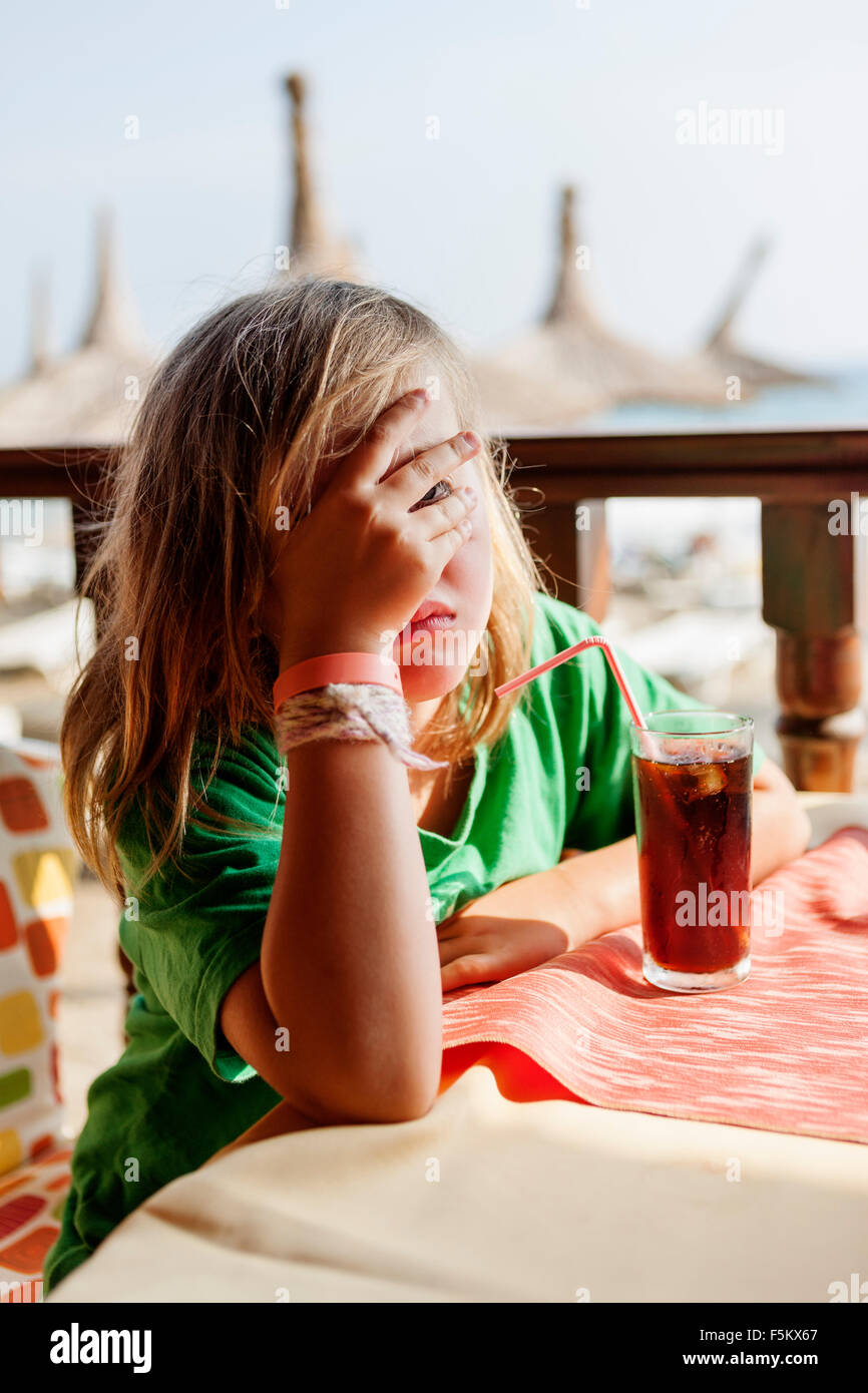 Turquie, Alanya, Girl (4-5) sitting at table et couvrant son visage avec la main Photo Stock