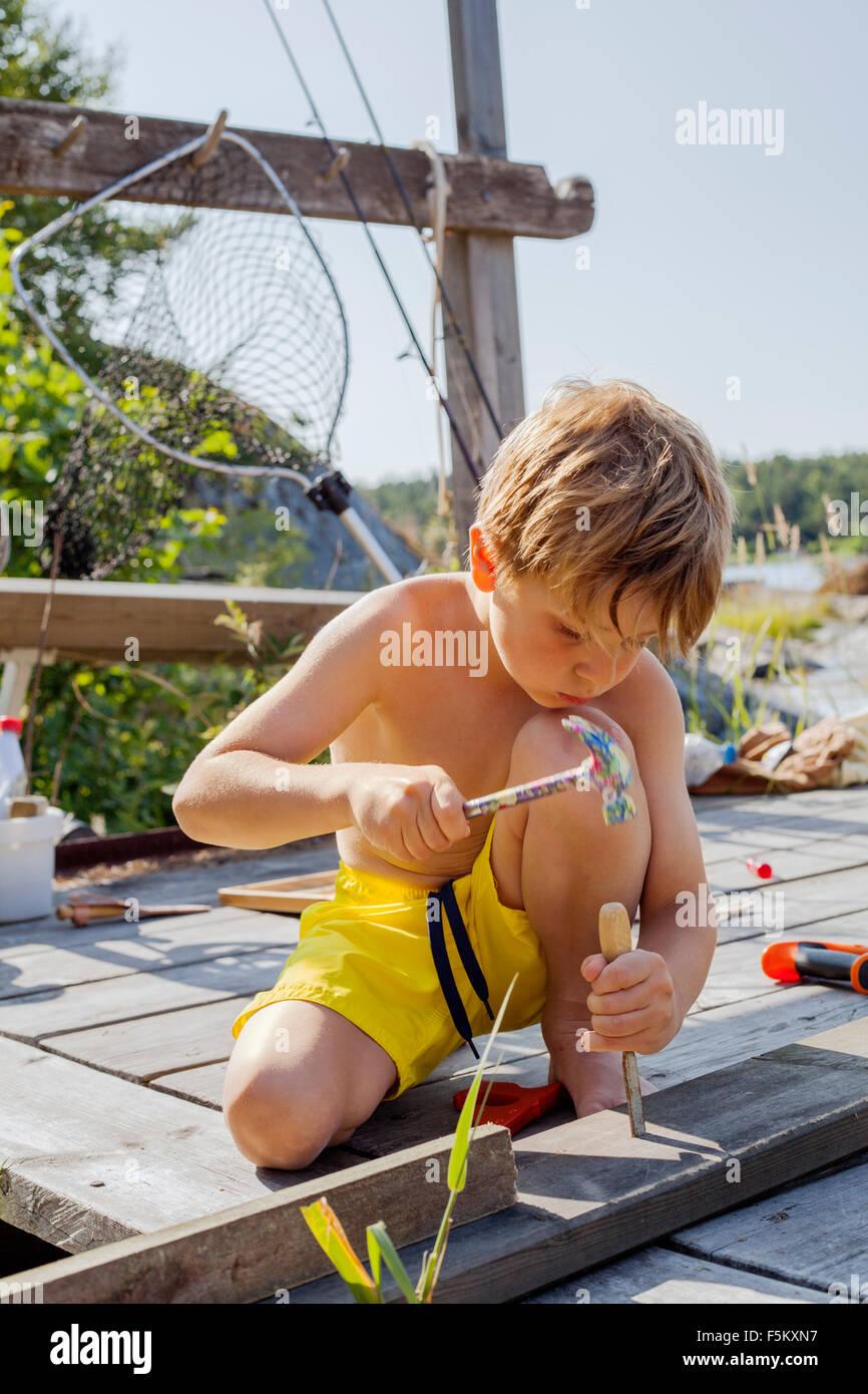La Suède, l'Uppland, Runmaro Barrskar, Garçon (4-5), la réparation de pont en bois Photo Stock