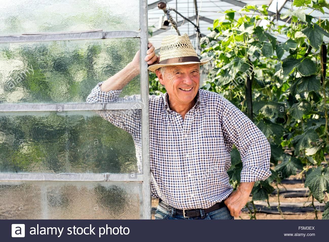 Senior man wearing hat appuyé contre la porte de hothouse looking at camera smiling Photo Stock