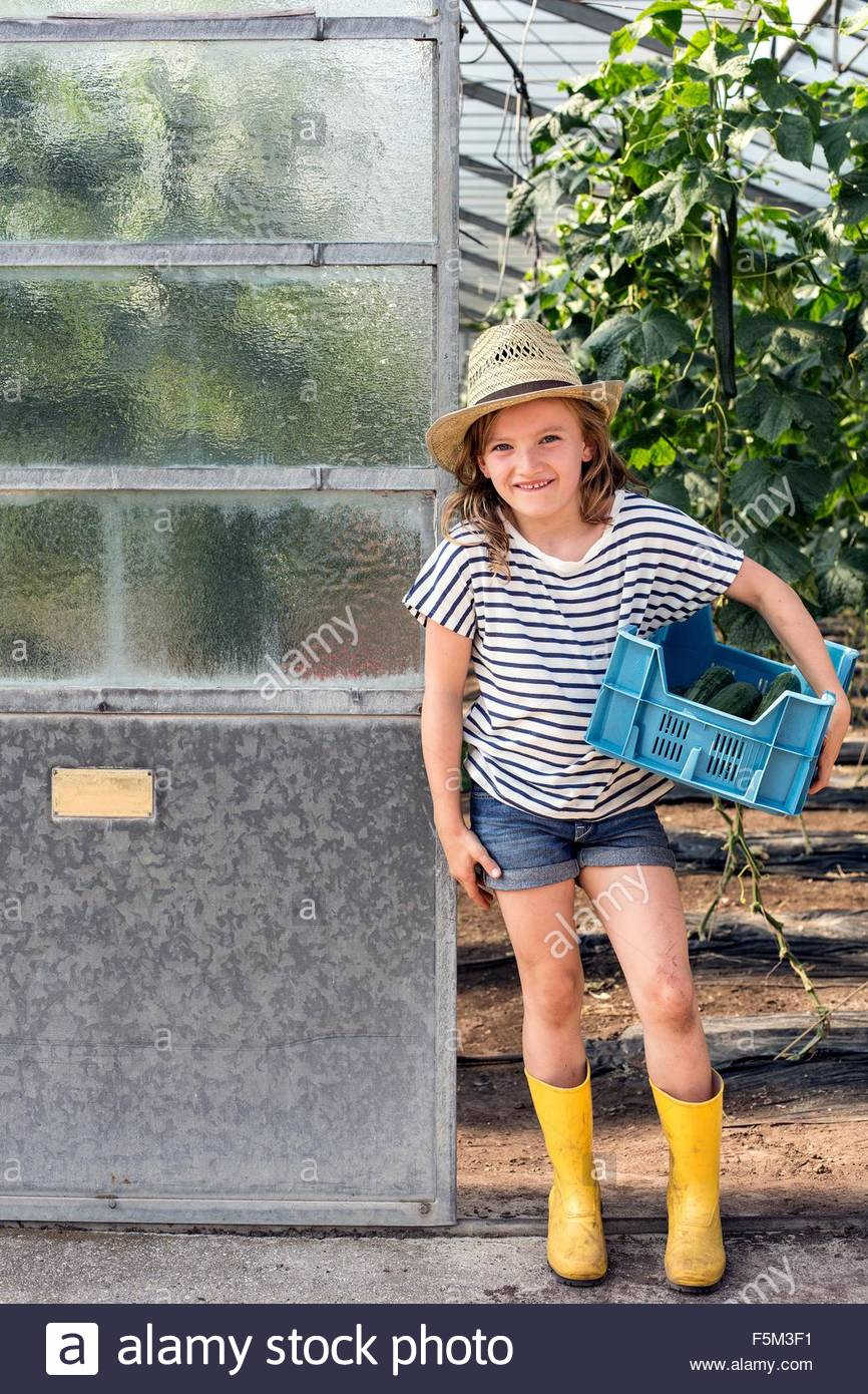 Girl wearing Wellington et hat standing in doorway hothouse holding tray looking at camera smiling Photo Stock