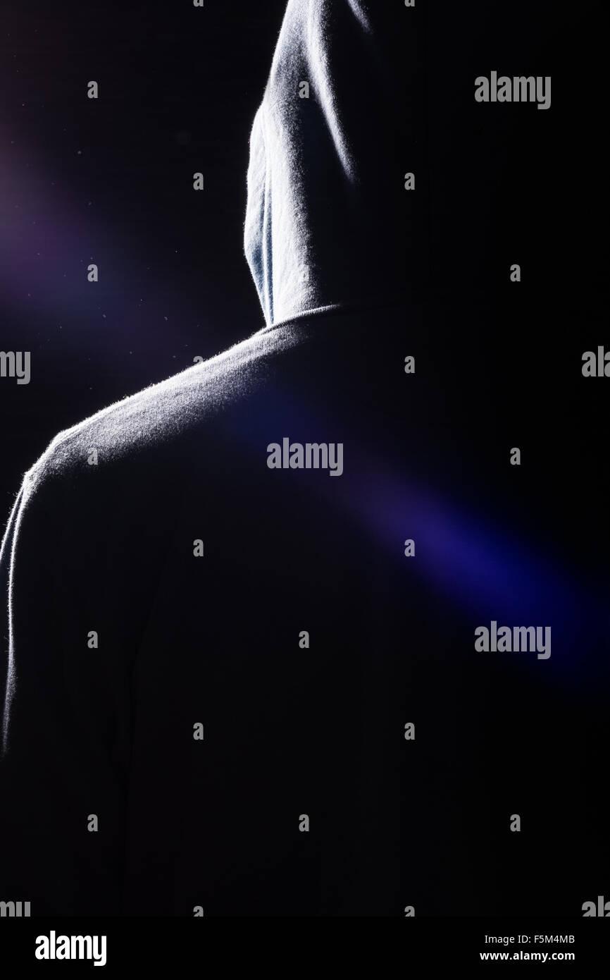 Une silhouette sombre d'un homme portant un sweat à capuche avec très ombres spectaculaires, des reflets et des poussières dans l'air. Banque D'Images
