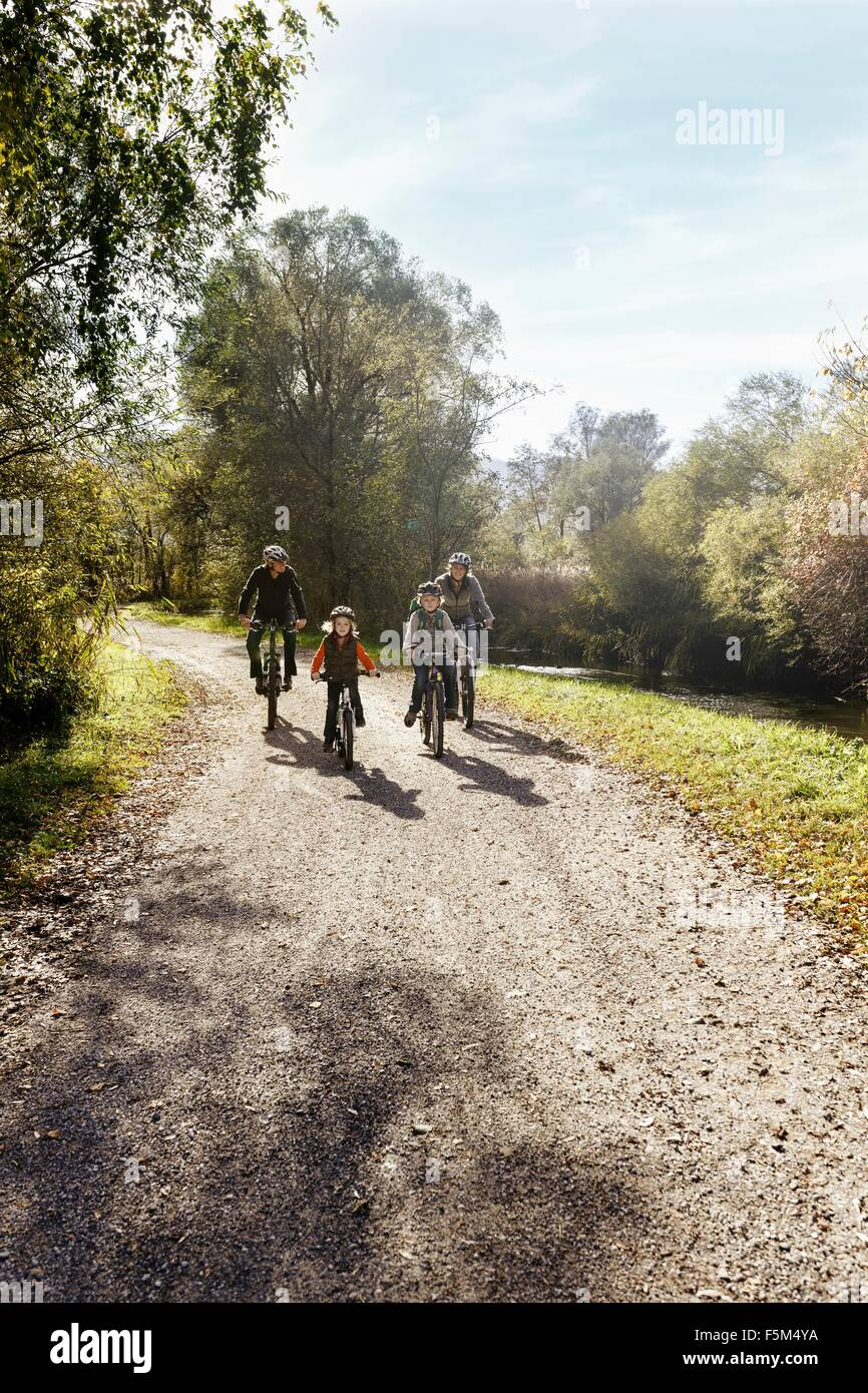 Vue avant du family riding bicycles on rural road Photo Stock