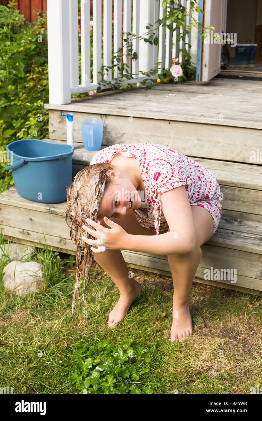 La Suède, l'archipel de Stockholm, Grasko, Girl (12-13) le lavage des cheveux à l'extérieur Photo Stock
