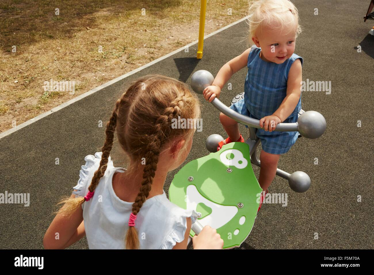 High angle view of sisters sitting on seesaw Photo Stock