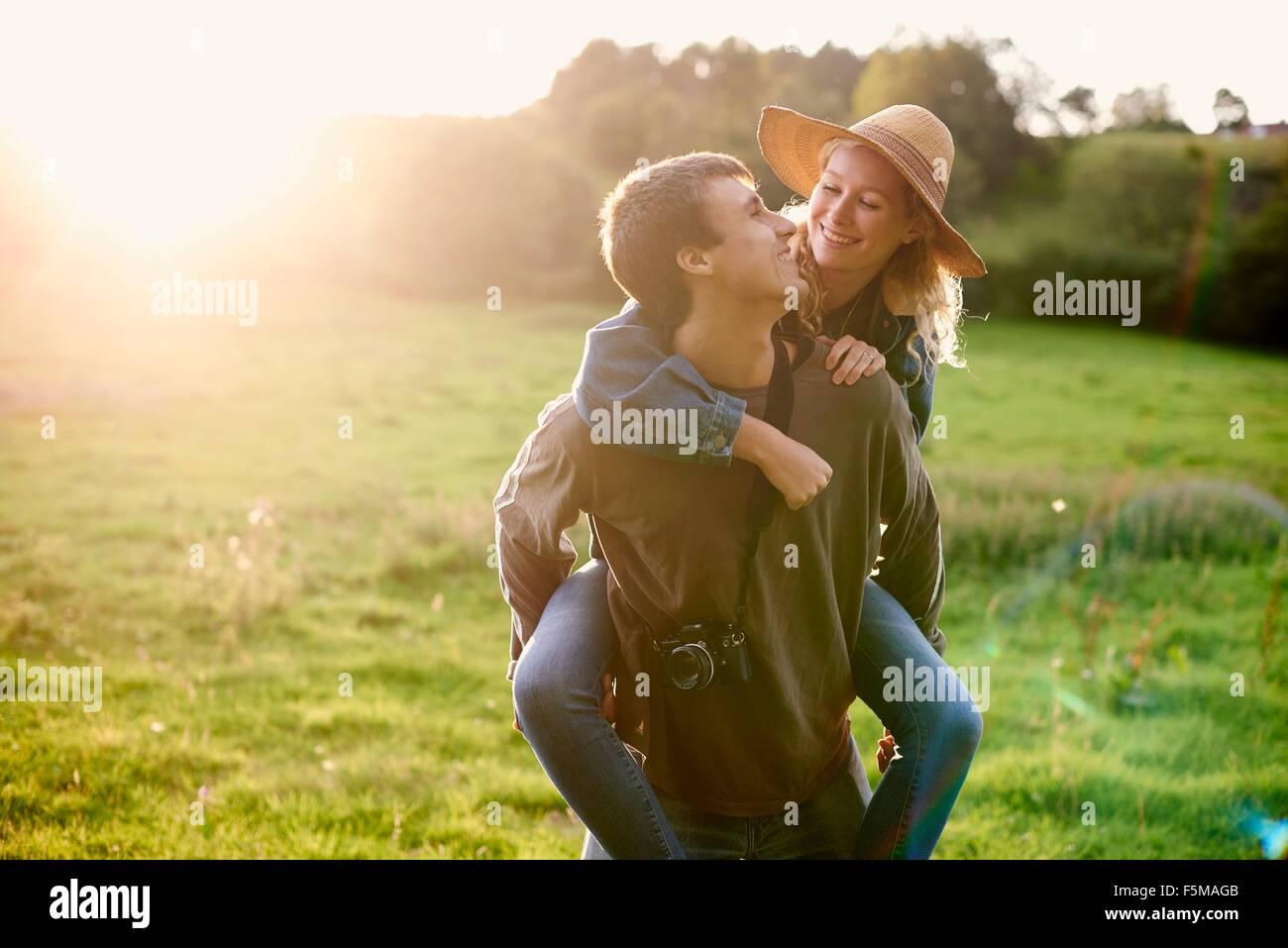 Young man giving girlfriend piggyback un in rural field Photo Stock