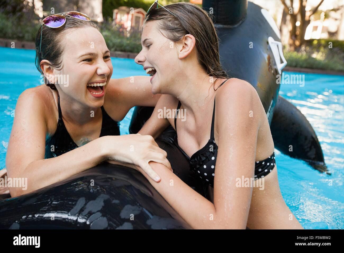 Deux adolescentes se tenant à pêcher dans une piscine gonflable Banque D'Images