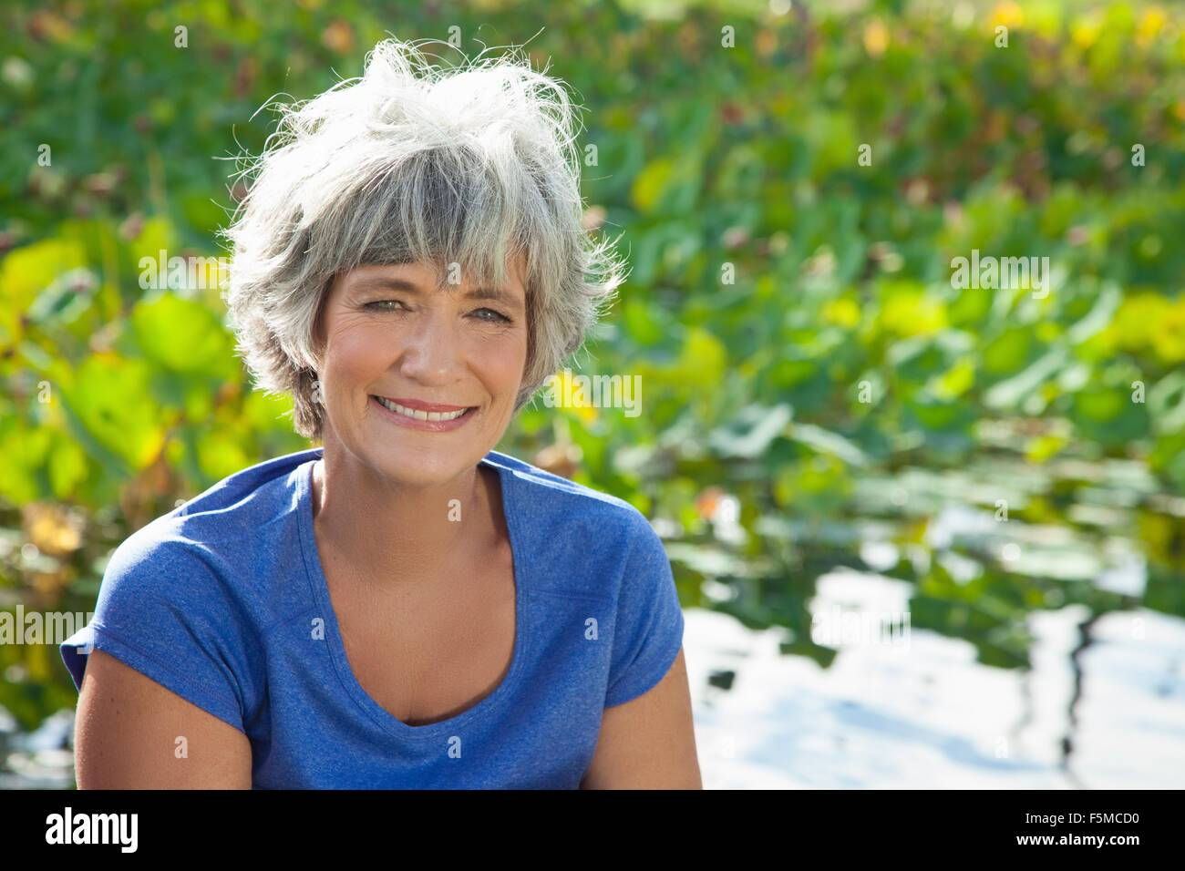 Portrait of young woman outdoors, smiling Photo Stock