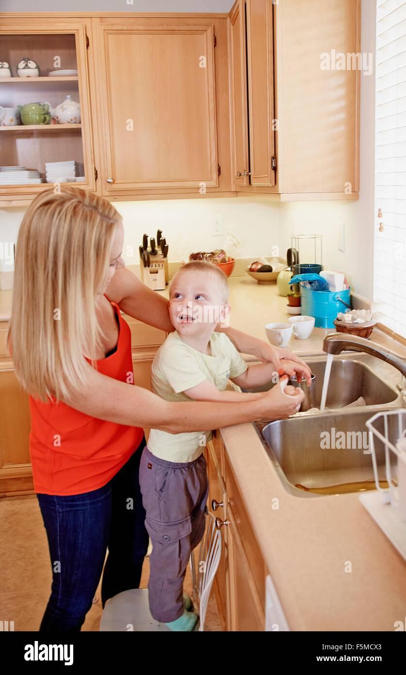 Laver les mains de mère fils dans un évier de cuisine Photo Stock