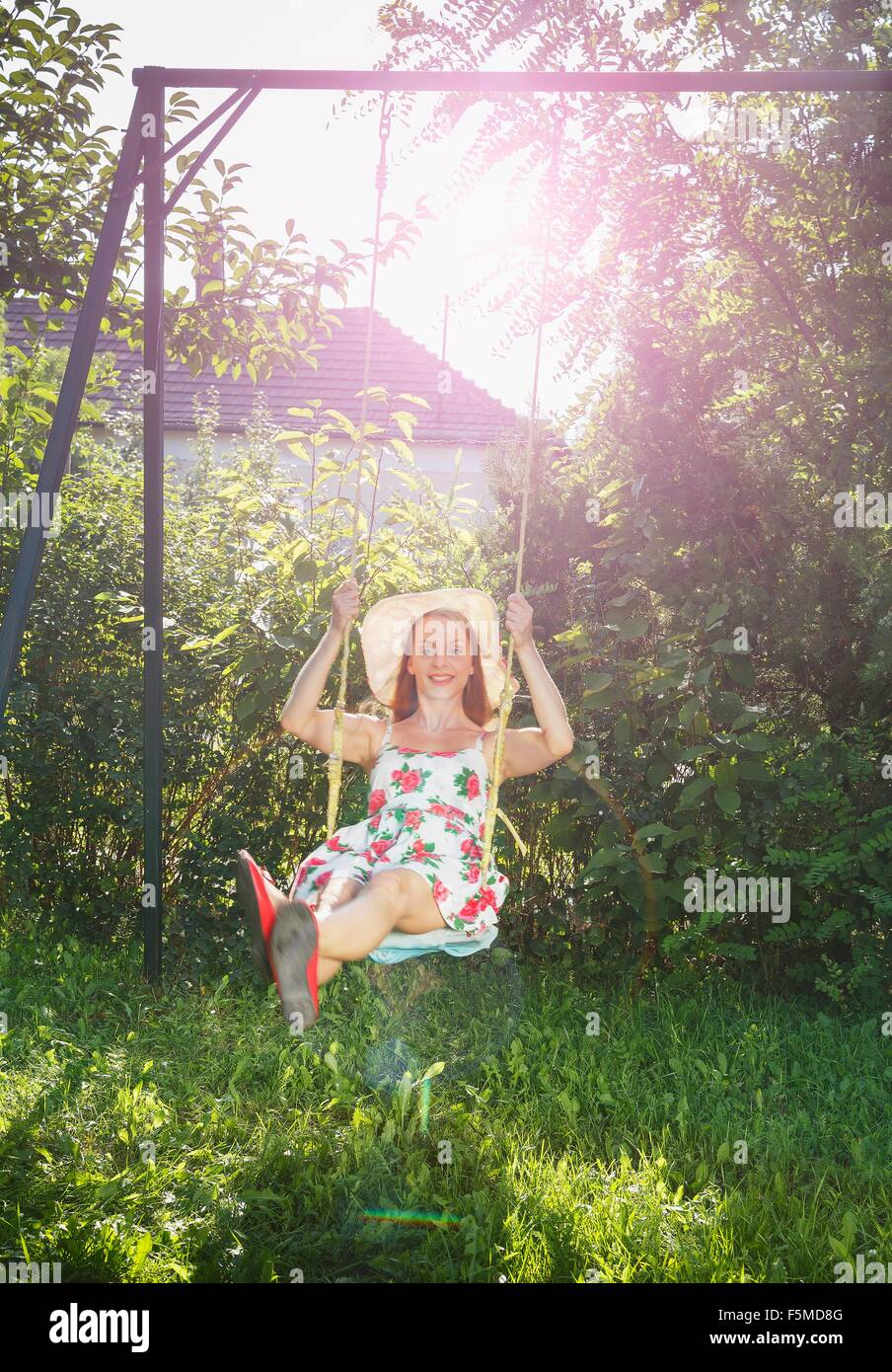 Mid adult woman swinging sur balançoire Photo Stock