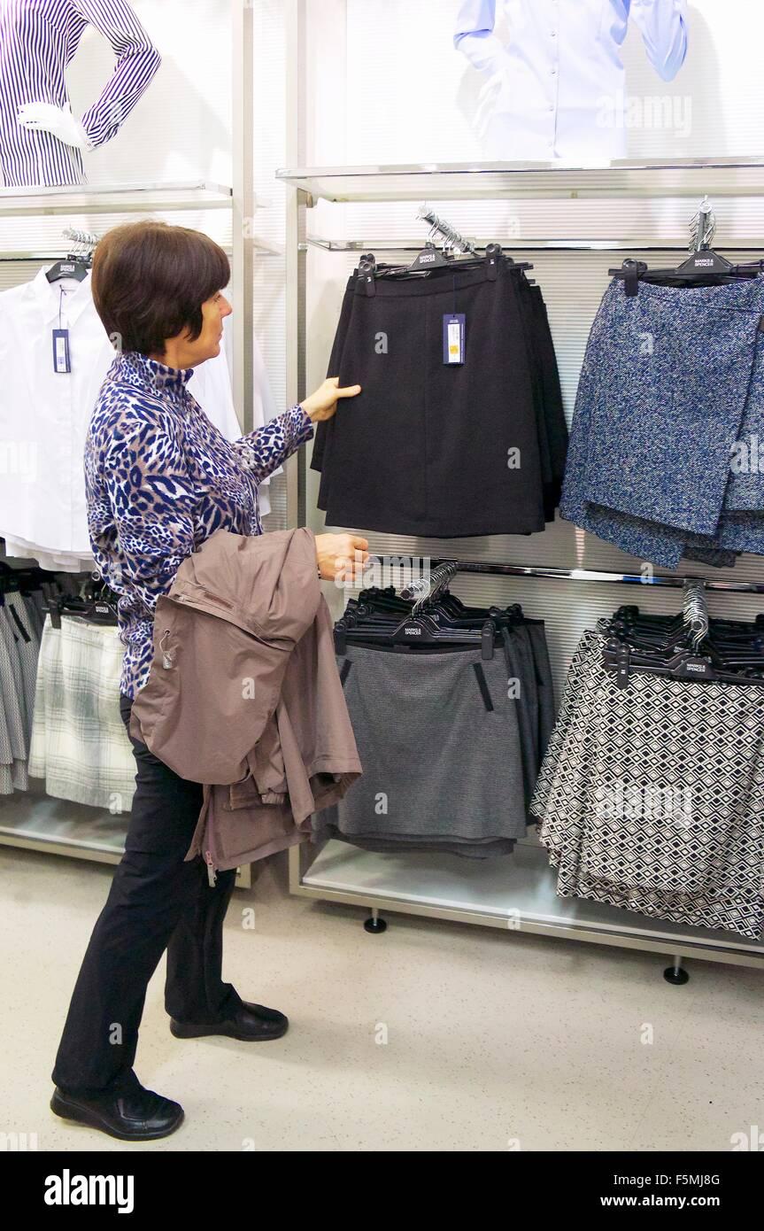 Femme d'âge moyen pour les achats dans un hypermarché de la jupe. Jupes de rails sur le mur. Photo Stock