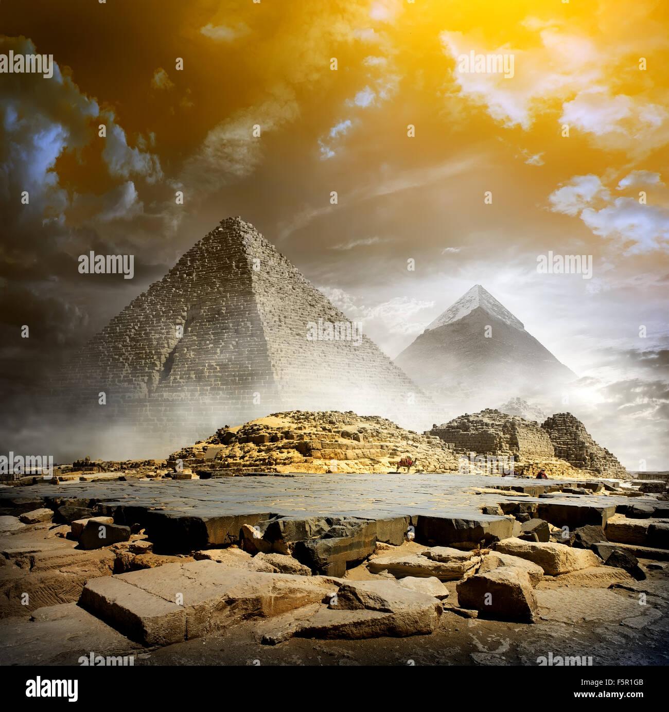 Les nuages de tempête et brouillard Orange plus de pyramides égyptiennes Photo Stock