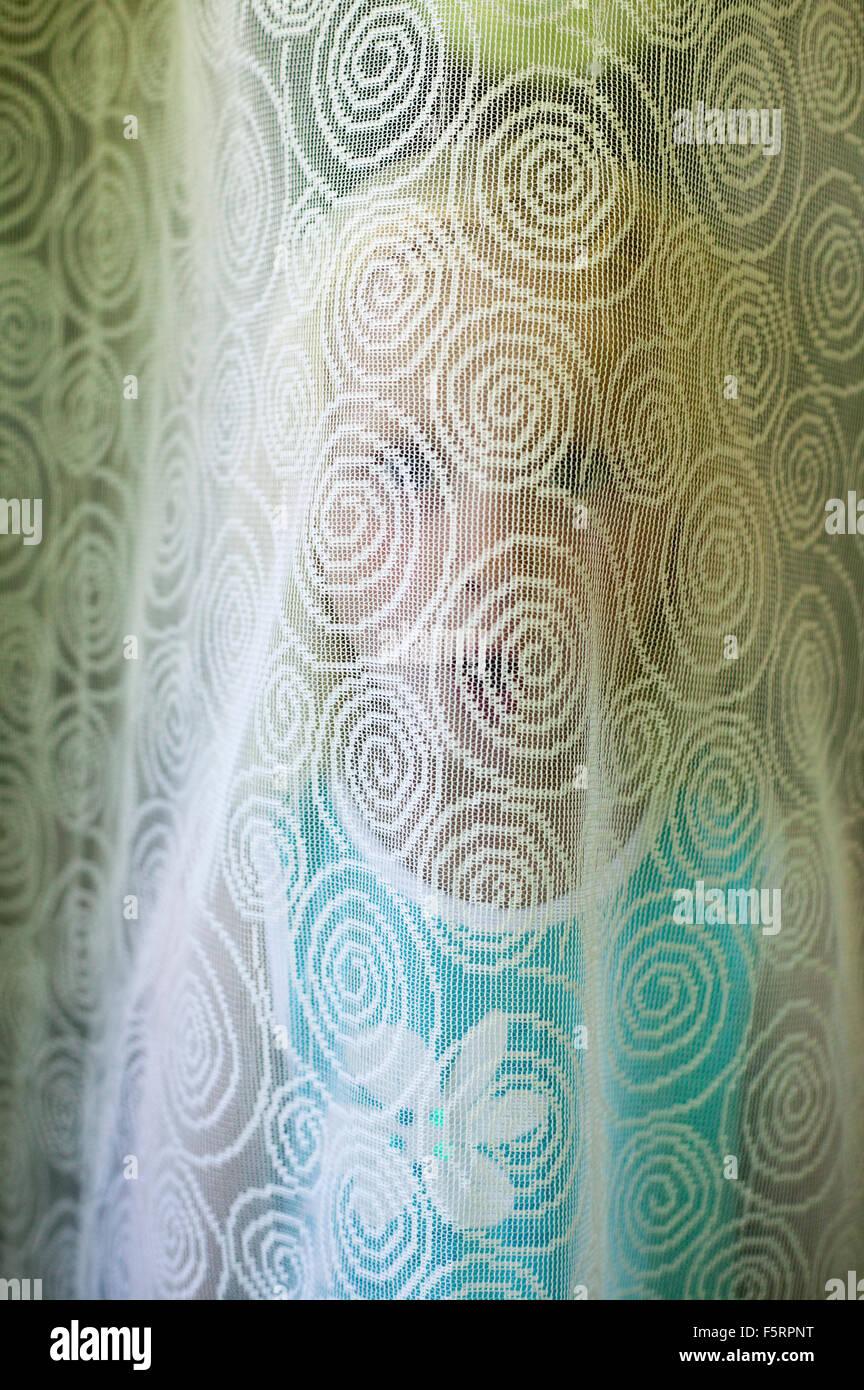 La Suède, Narke, Filipshyttan, Portrait of Girl (4-5) se cacher derrière le rideau Photo Stock