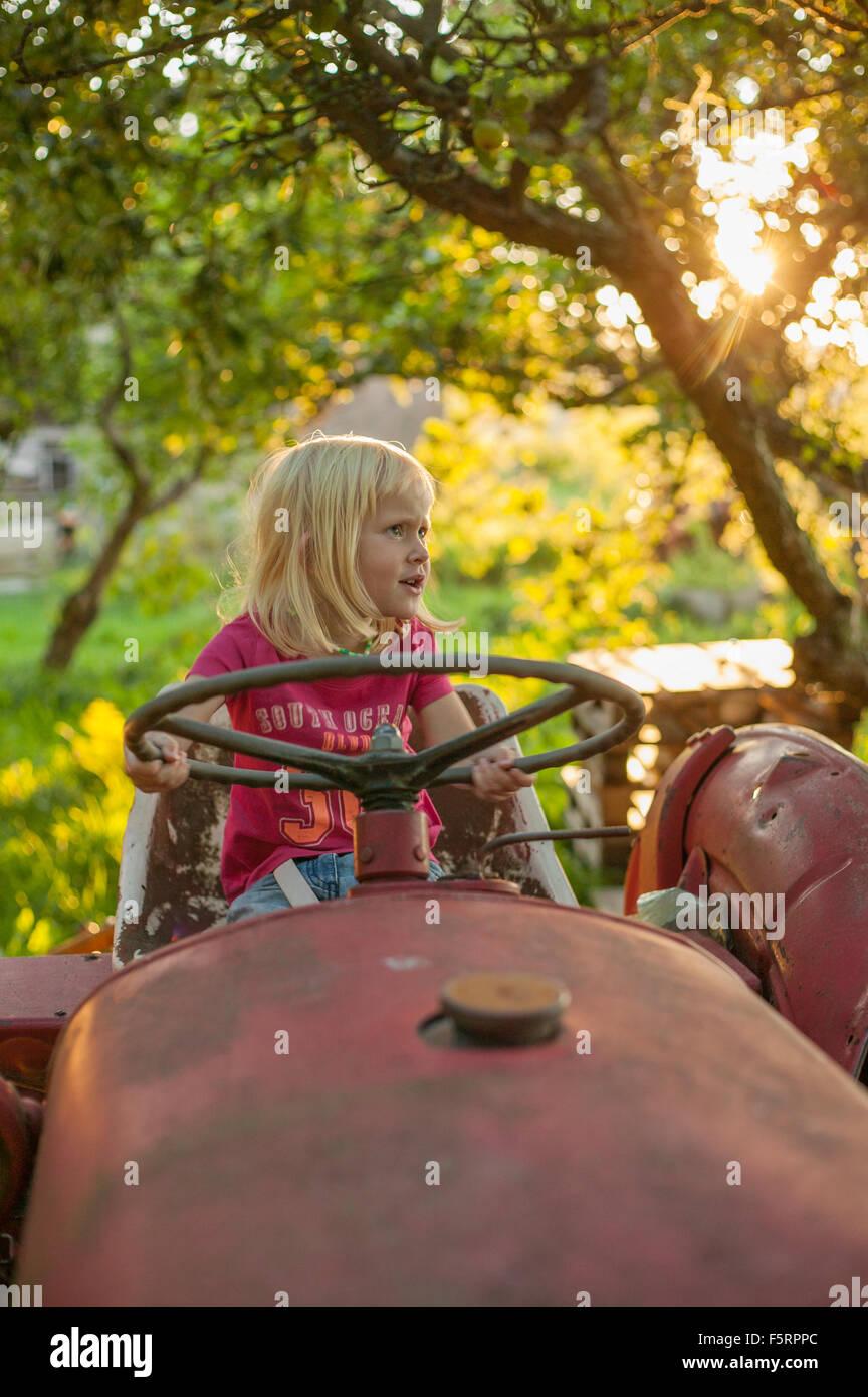 La Suède, Skane, Osterlen, Girl (4-5) sur le tracteur Photo Stock