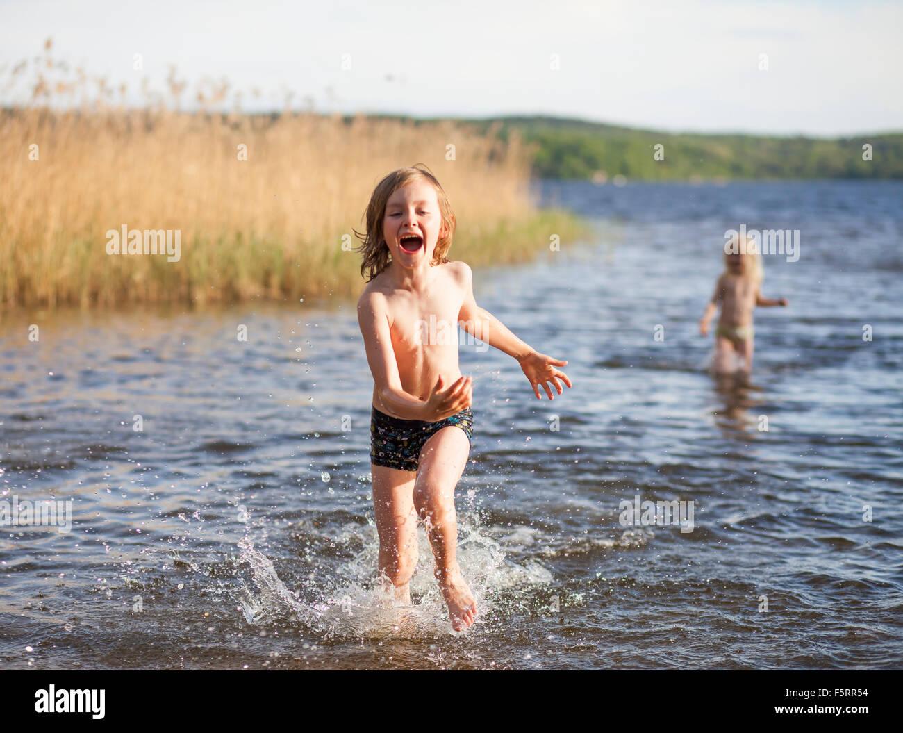 La Suède, Vastergotland, Lerum, lac Aspen, Boy (8-9) et (6-7) à l'affiche dans le lac Banque D'Images
