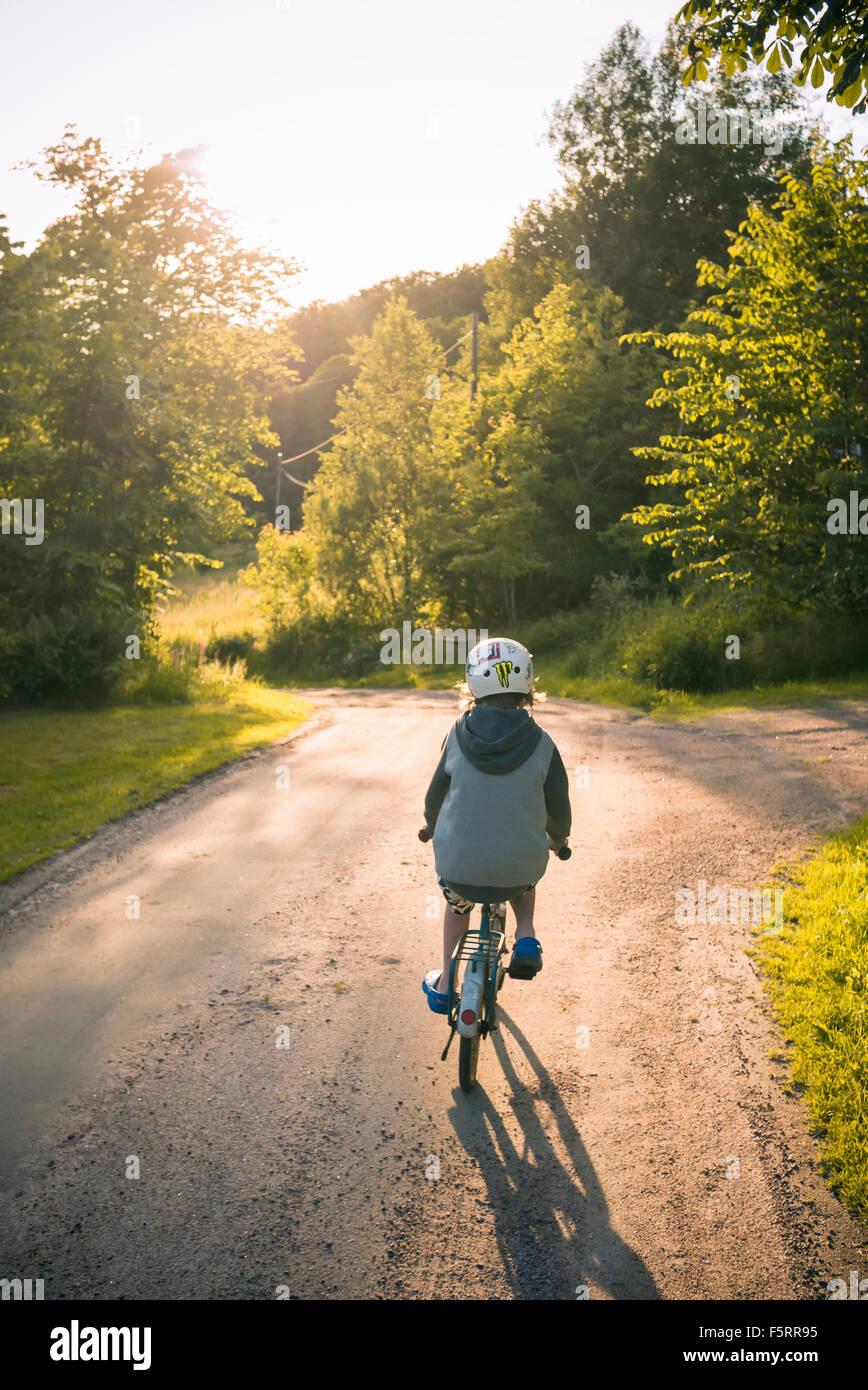 La Suède, Bohuslan, Halleback, Boy (10-11) à vélo le long de la route d'asphalte Photo Stock