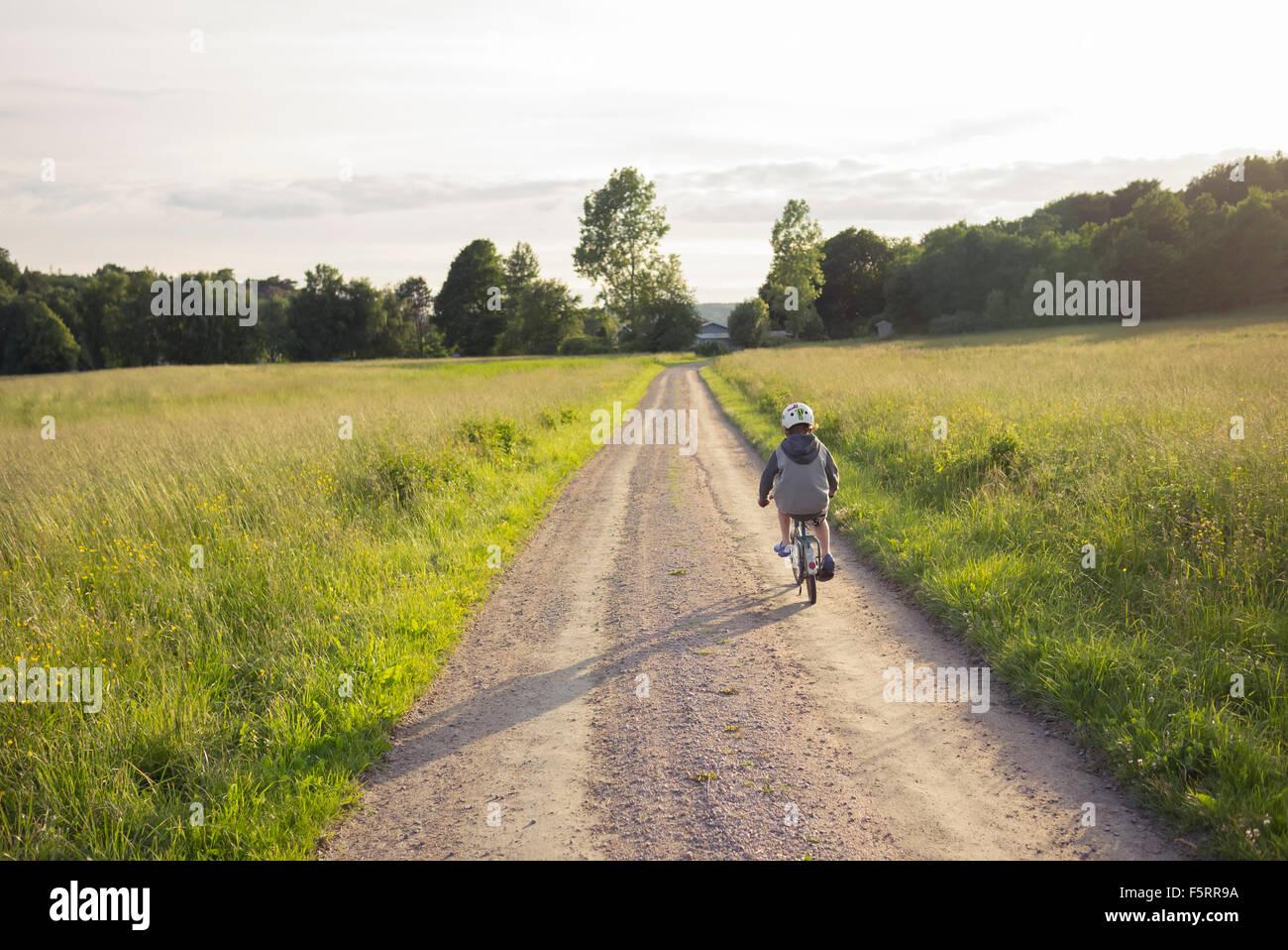 La Suède, Bohuslan, Halleback, Boy (10-11) à vélo le long de la route menant de la terre à travers Photo Stock
