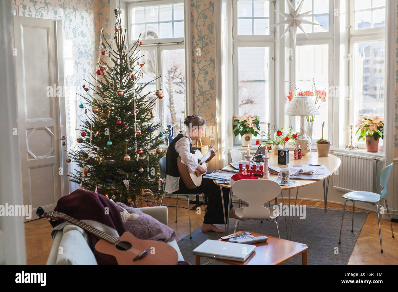La Suède, Senior woman playing guitar in living room Photo Stock