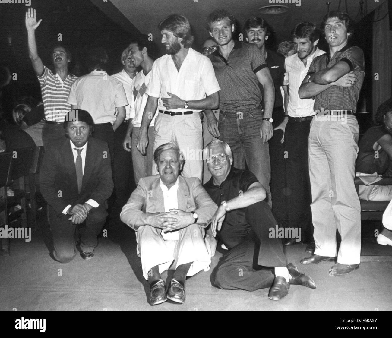 Le chancelier allemand Helmut Schmidt (L) et l'entraîneur de l'équipe nationale allemande Jupp Derwald (R) sont assis sur le sol en face des joueurs de l'équipe de football allemande dans un hôtel à Madrid le 12 juillet 1982. L'équipe nationale allemande avait perdu la finale du championnat du monde de football contre l'Italie avec 1:3 buts la veille. Derrière le Chancelier et l'entraîneur (R-L): Klaus Fischer, Wolfgang Dremmler, Wilfried Hannes, Hans-Peter Briegel, Manfred Kaltz, Hans Müller, et Uli Stielike. Banque D'Images