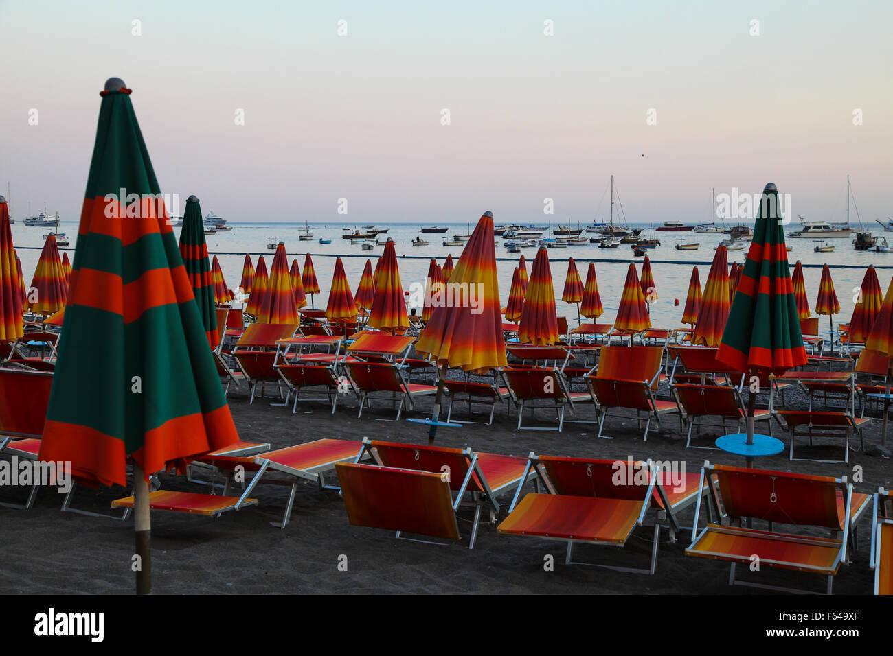 Beach brollies repliée vers le bas pour la nuit, sun set lueur rouge dans le ciel de la fin d'une autre Photo Stock