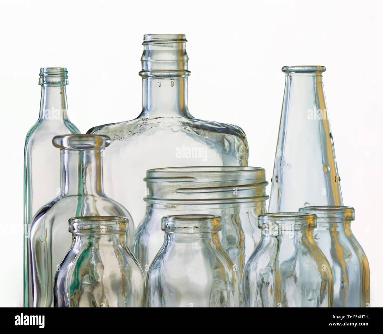 Bouteilles en verre et de forme différentes, montrant la réfraction sur fond blanc. La qualité lumineuse Photo Stock