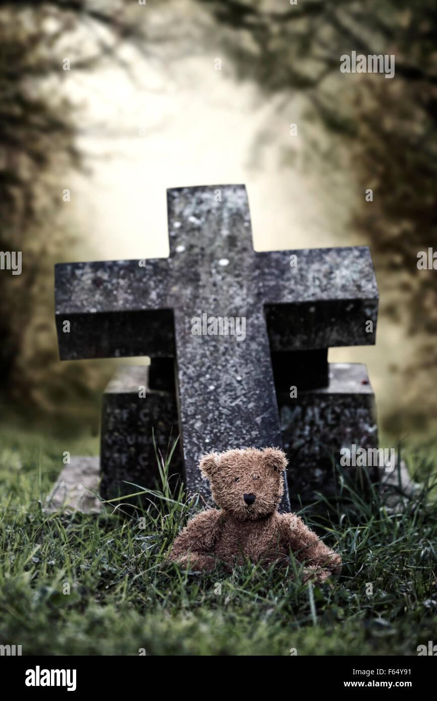 Une tombe avec un ours en peluche Photo Stock