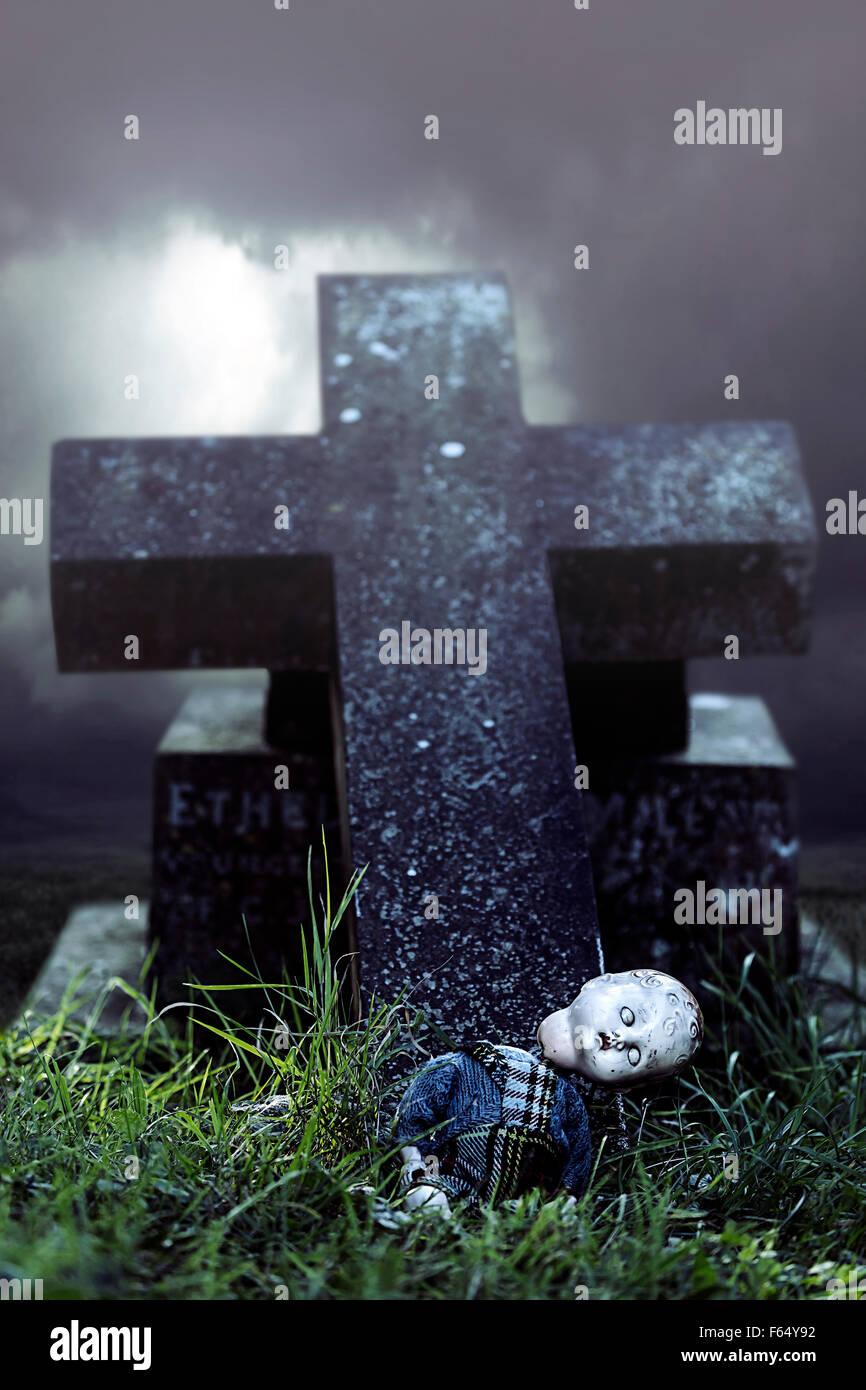 Une poupée cassée sur une tombe Photo Stock