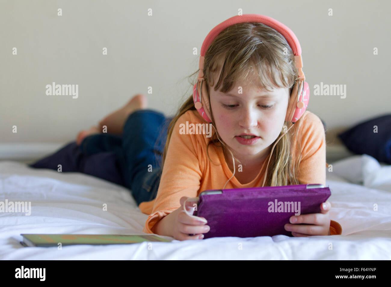 Fille de travailler sur iPad mini avec des écouteurs Photo Stock