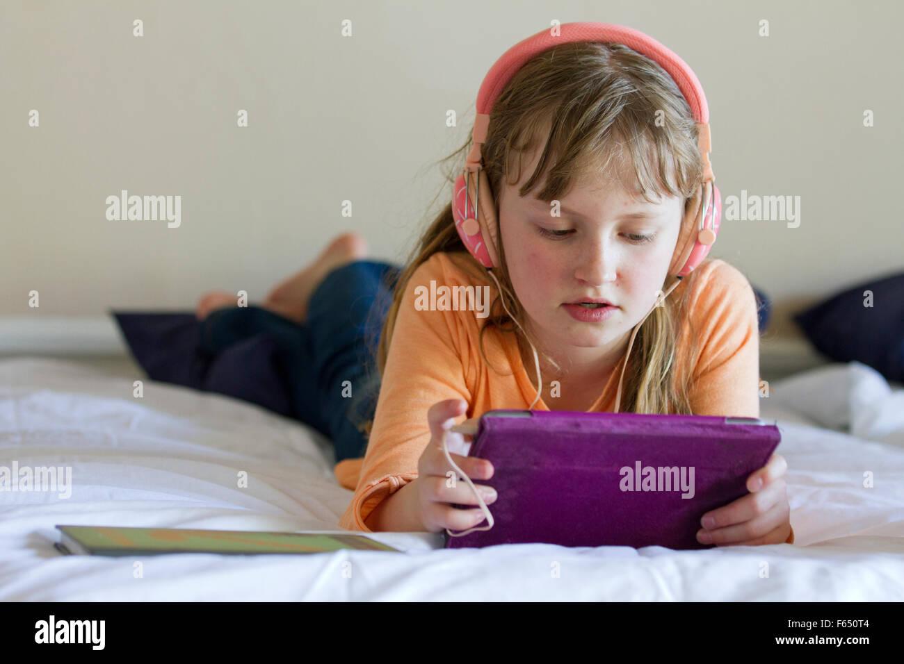 Fille de travailler sur iPad mini avec écouteurs rose Photo Stock