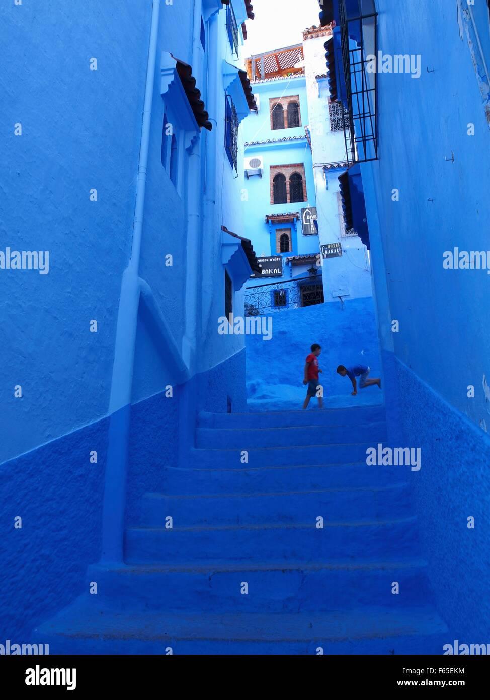 Enfants jouant dans une ruelle bleue dans la Médina de Chefchaouen, Maroc Photo Stock