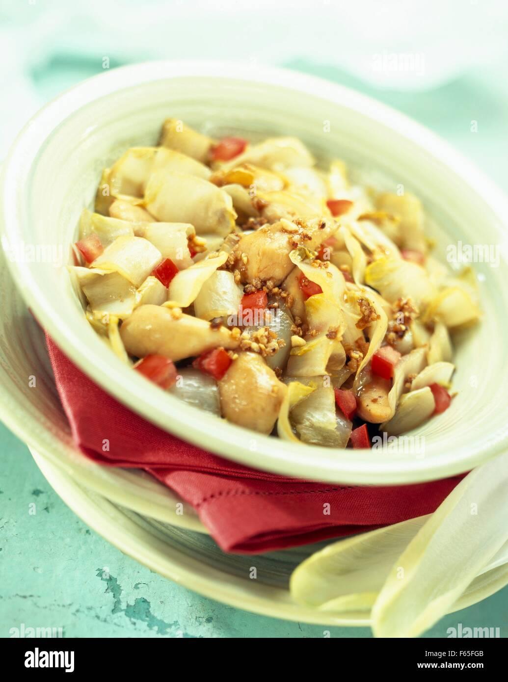 Poêlée de chicons avec poulet et arachides Banque D'Images