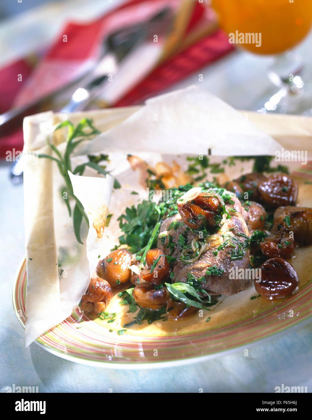 Steak d'autruche aux châtaignes et aux herbes cuit dans du papier ciré Banque D'Images