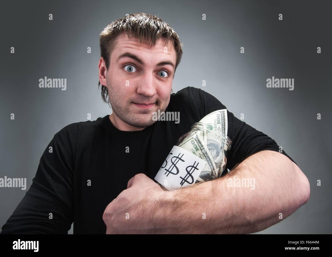 Homme étrange se tient avec pot plein de dollars sur gray Photo Stock