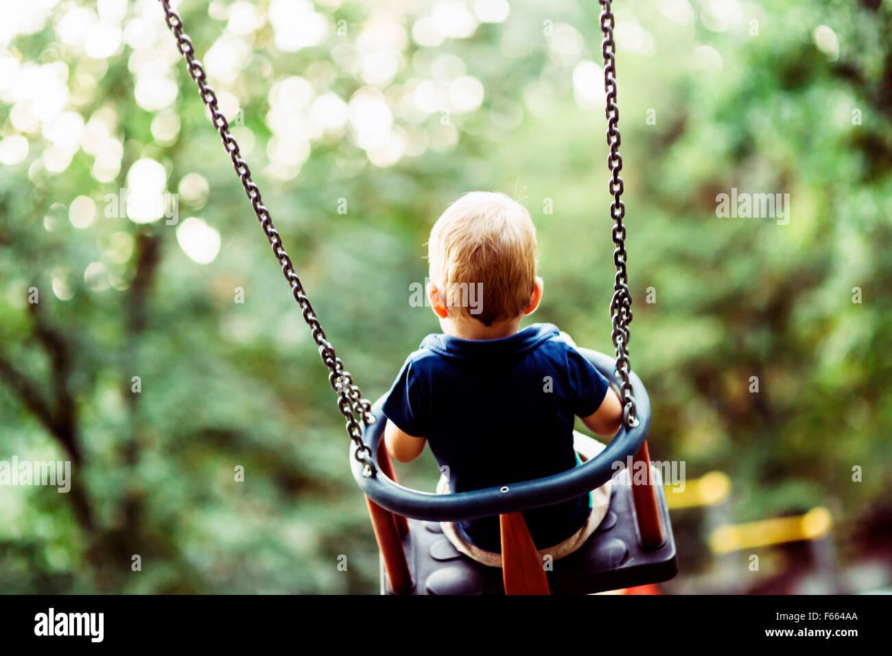 Enfant espiègle sur l'extérieur, swing shot de derrière Photo Stock