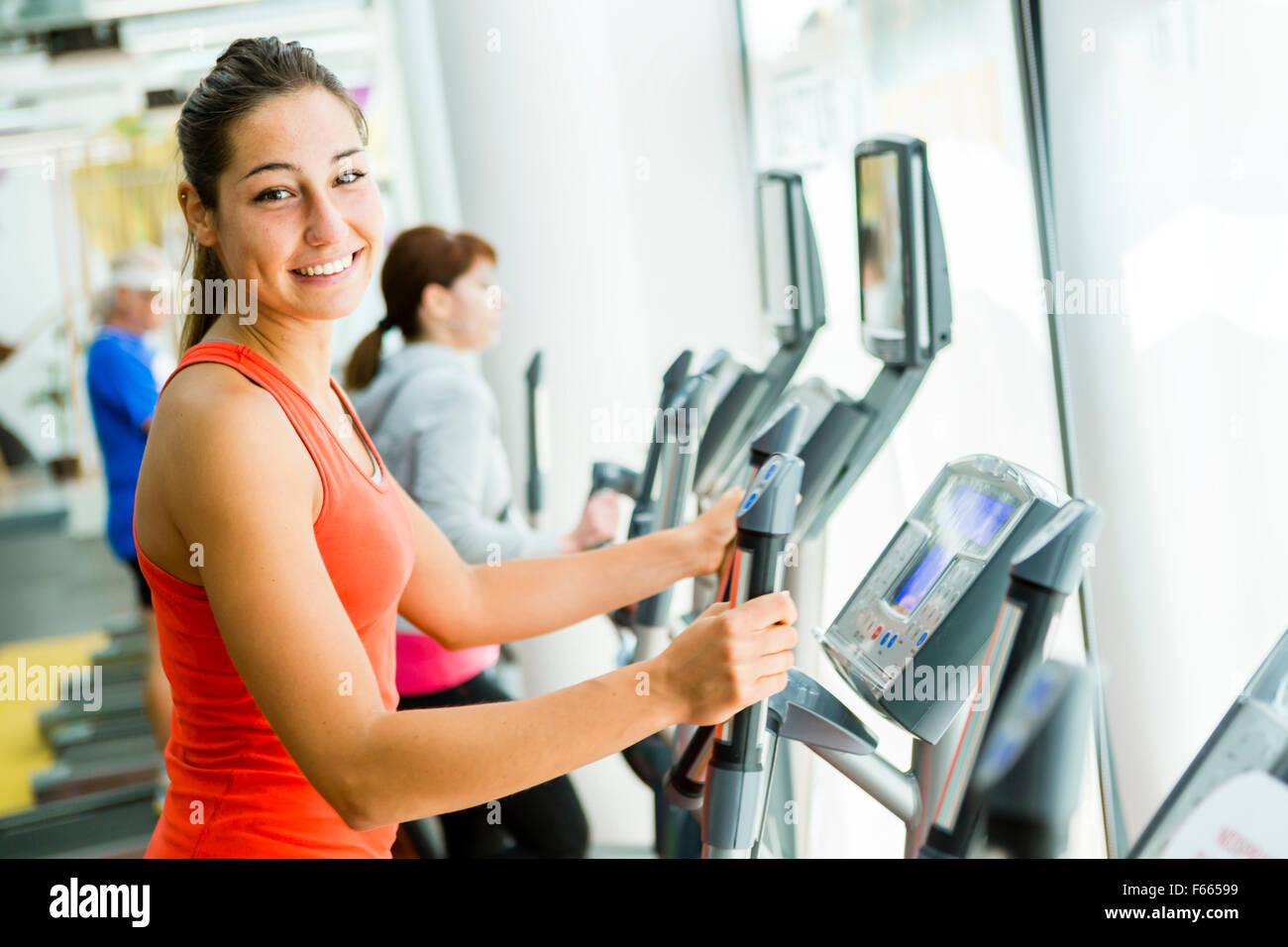 Jeune femme fit à l'aide d'un entraîneur elliptique dans un centre de remise en forme et souriant Photo Stock