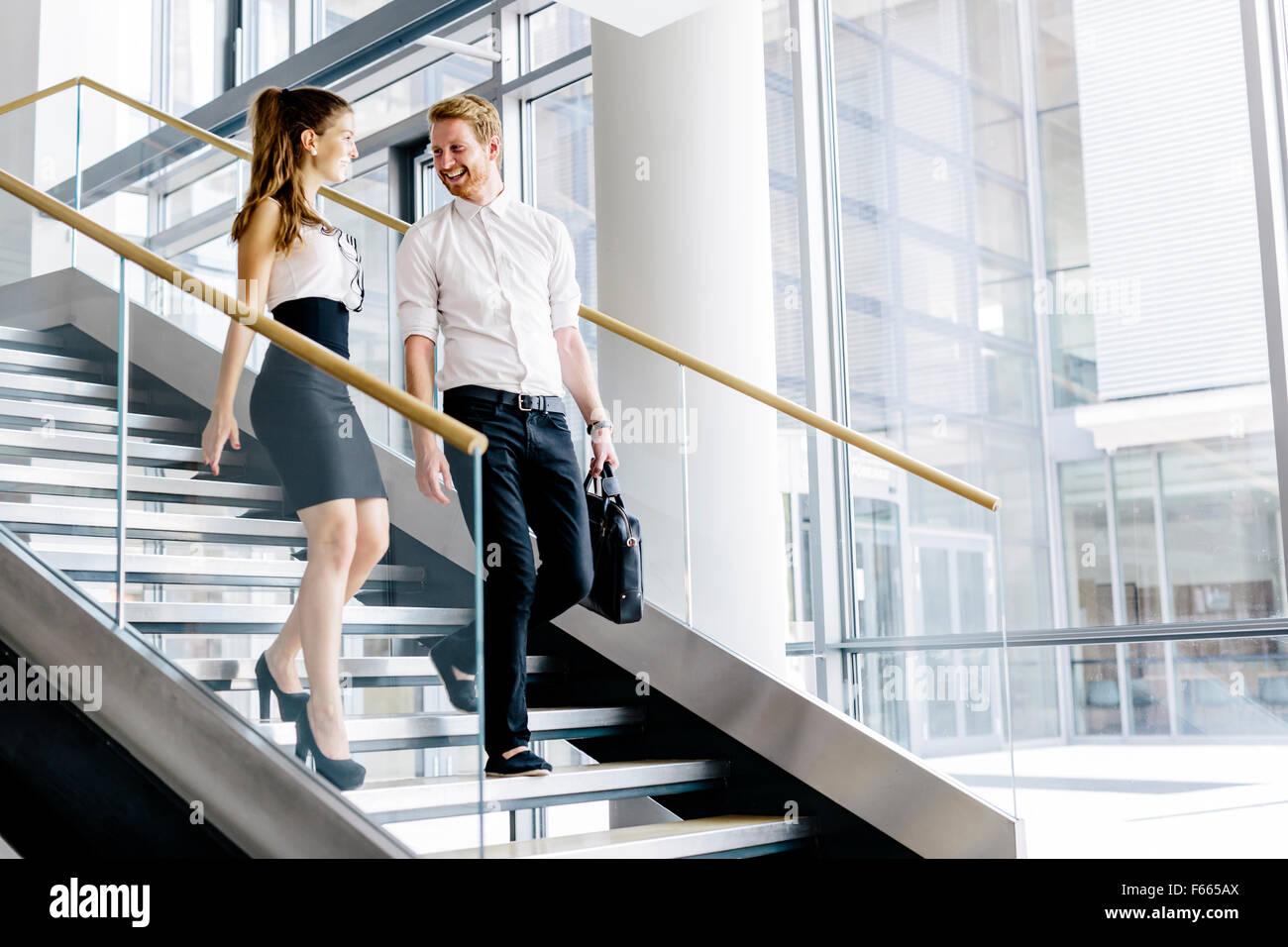 Des collègues de parler dans les escaliers et le flirt Photo Stock