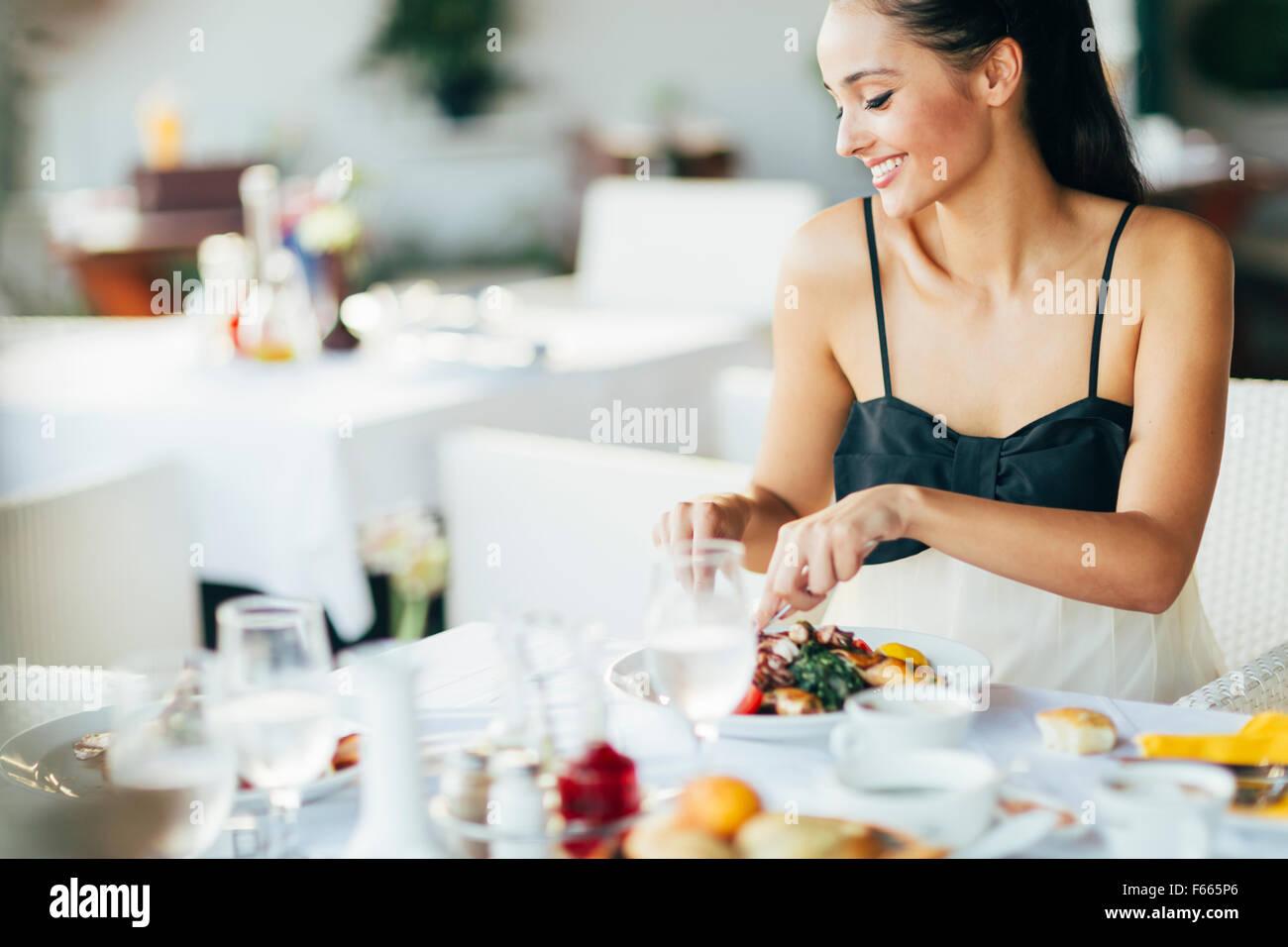 Attractive Woman eating in outdoor restaurant Photo Stock