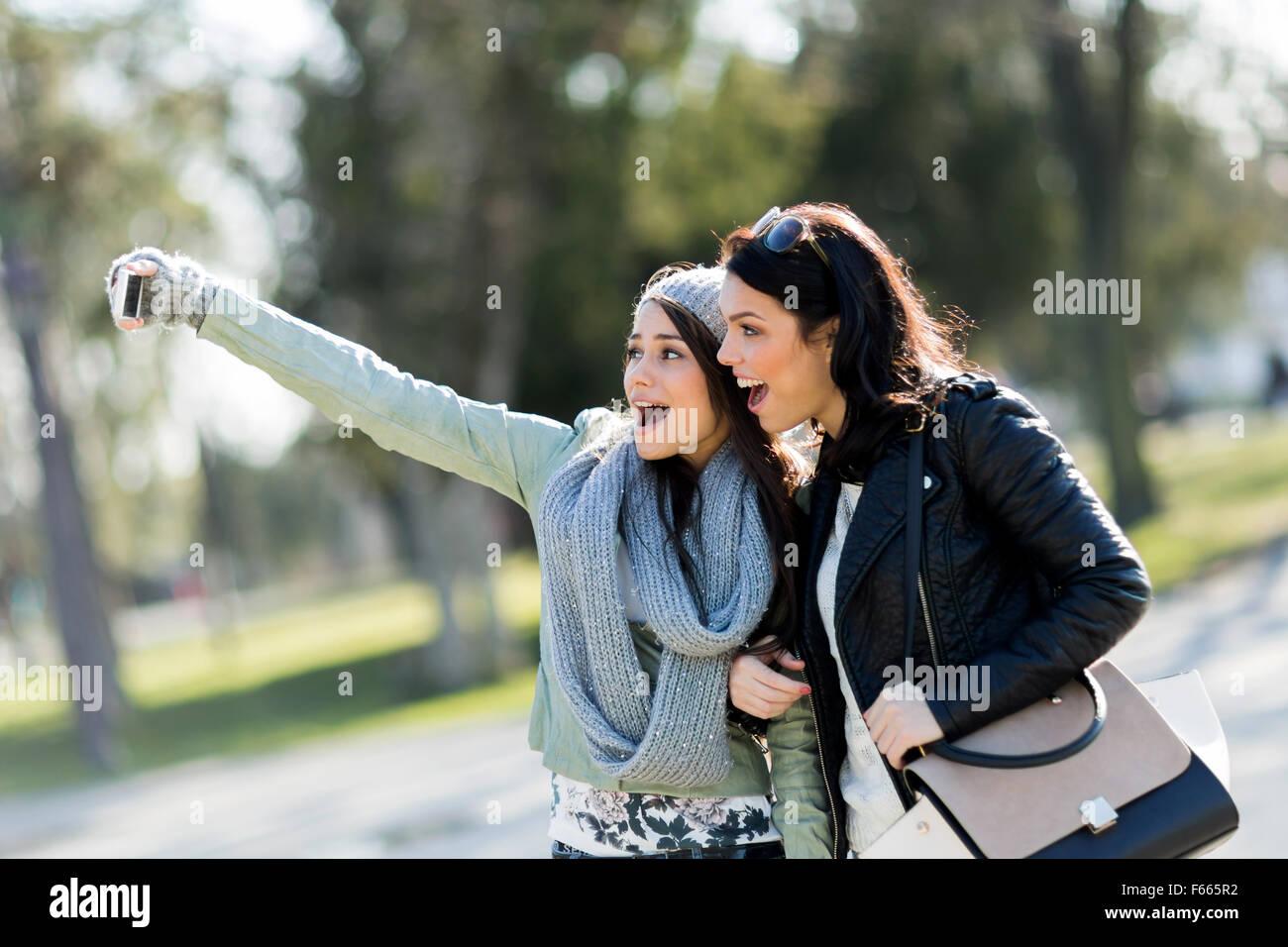 Deux jeunes femmes prenant une des selfies eux-mêmes sur une journée ensoleillée Photo Stock