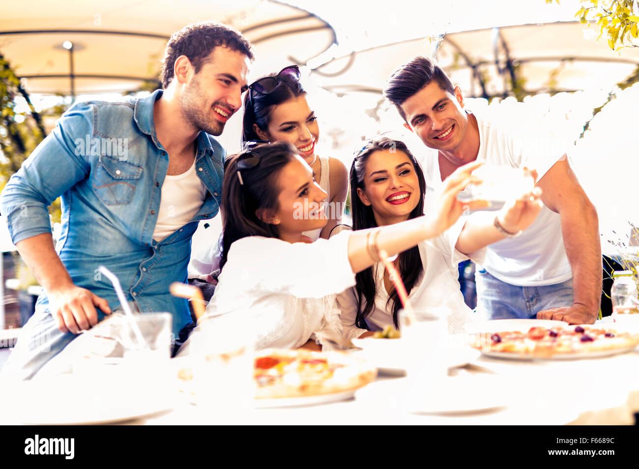 Groupe de jeunes gens assis dans un beau restaurant et prendre un en souriant selfies Banque D'Images